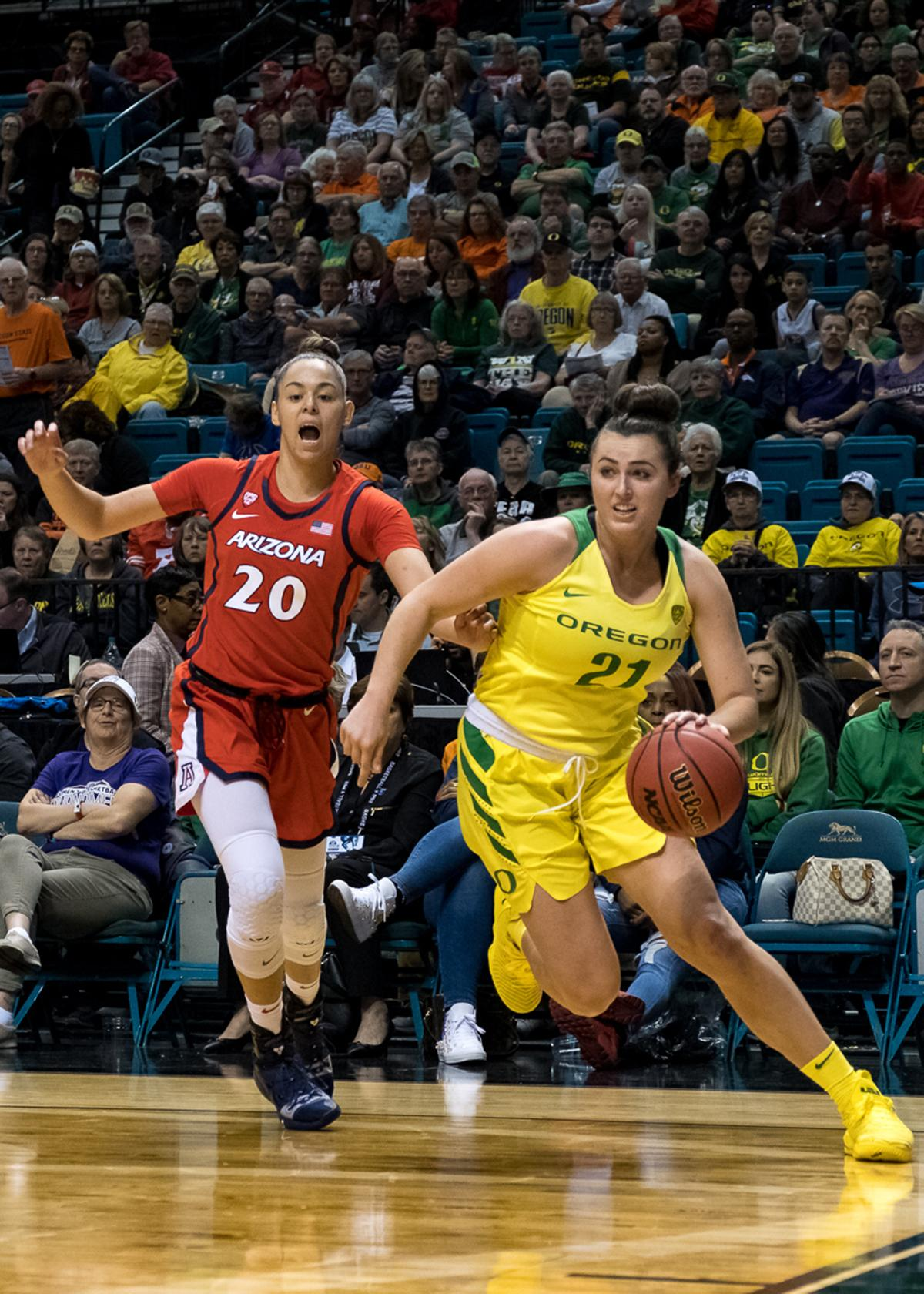 Ducks Erin Boley (#21) drives past Arizona's Dominique McBryde (#20) during Friday's game at MGM Arena. The number one seeded Oregon Ducks defeated the 8th seeded Arizona Wildcats 77-63 today in the quarterfinals of the Pac-12 Tournament in Las Vegas, Nevada. Two ducks logged double doubles with Ruthy Hebard leading the Ducks in scoring with 21 points and 10 rebounds while Sabrina Ionescu ended the game with 18 points, 13 assists and eight rebounds to help the 6th ranked Ducks move on to tomorrows semifinal match against UCLA at MGM Arena. Photo by Jeff Dean