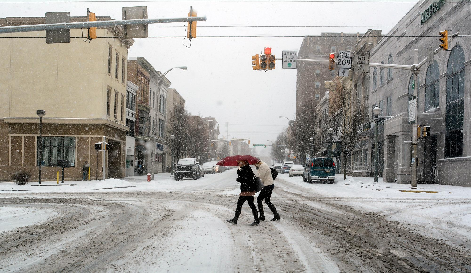 Pedestrians walk across a snow covered Centre Street in Pottsville, Pa., Wednesday, Feb. 20, 2019.(Andy Matsko/Republican-Herald via AP)