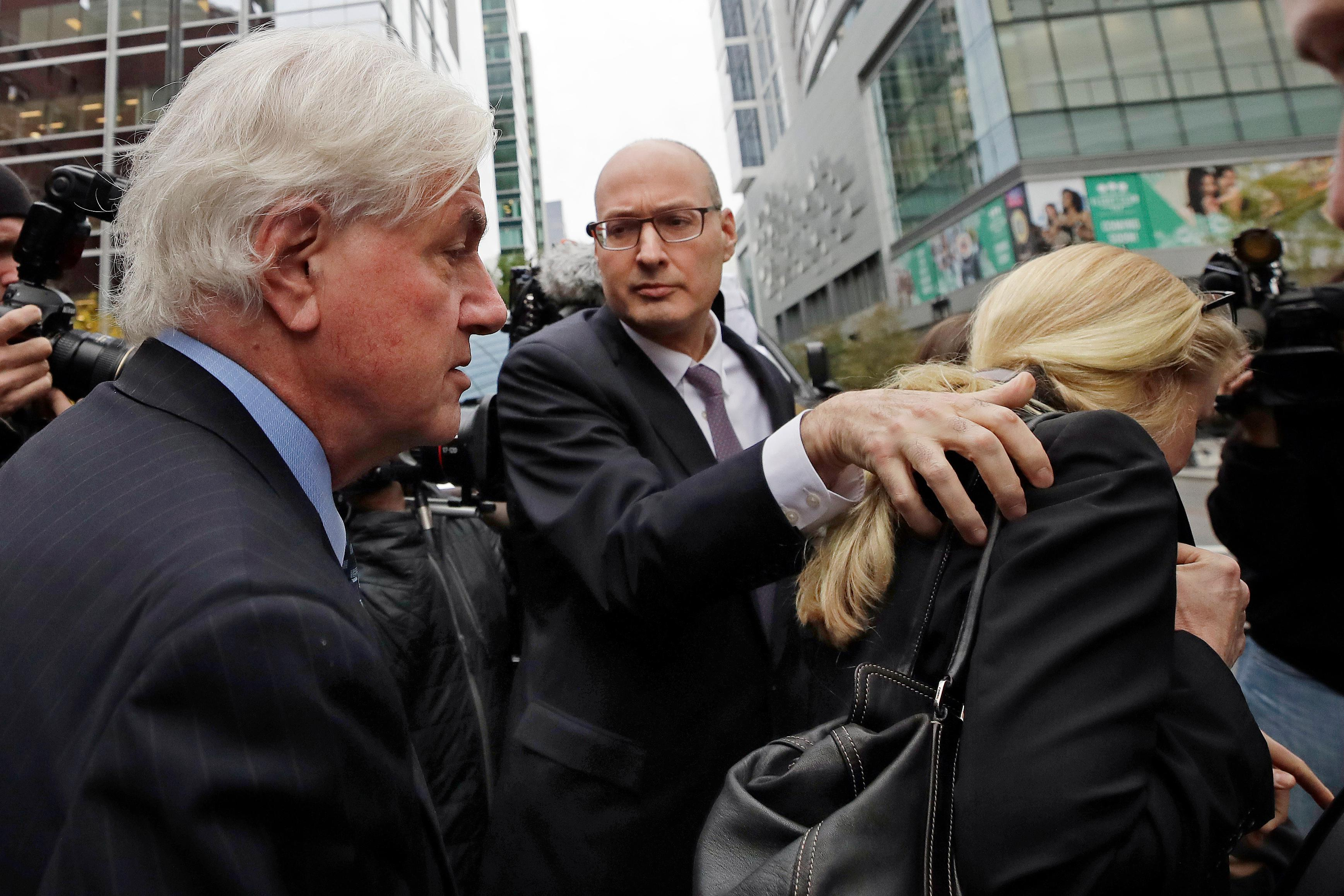 Gregory Abbott, far left, and his wife Marcia, far right, get into a car as they leave federal court after their sentencing in a nationwide college admissions bribery scandal, Tuesday, Oct. 8, 2019, in Boston. (AP Photo/Elise Amendola)