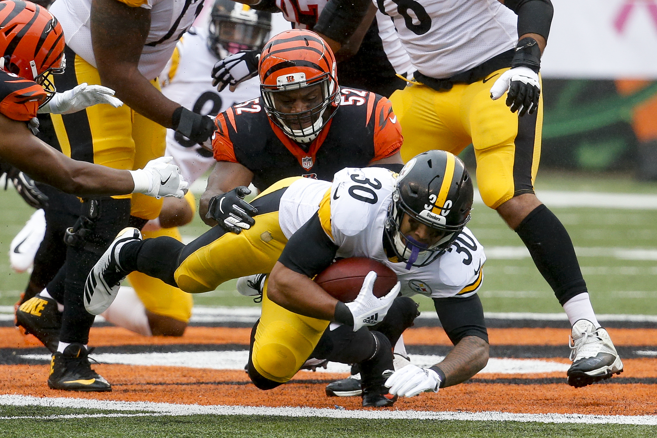 Pittsburgh Steelers running back James Conner (30) dives for extra yards against Cincinnati Bengals linebacker Preston Brown (52) in the first half of an NFL football game, Sunday, Oct. 14, 2018, in Cincinnati. (AP Photo/Frank Victores)