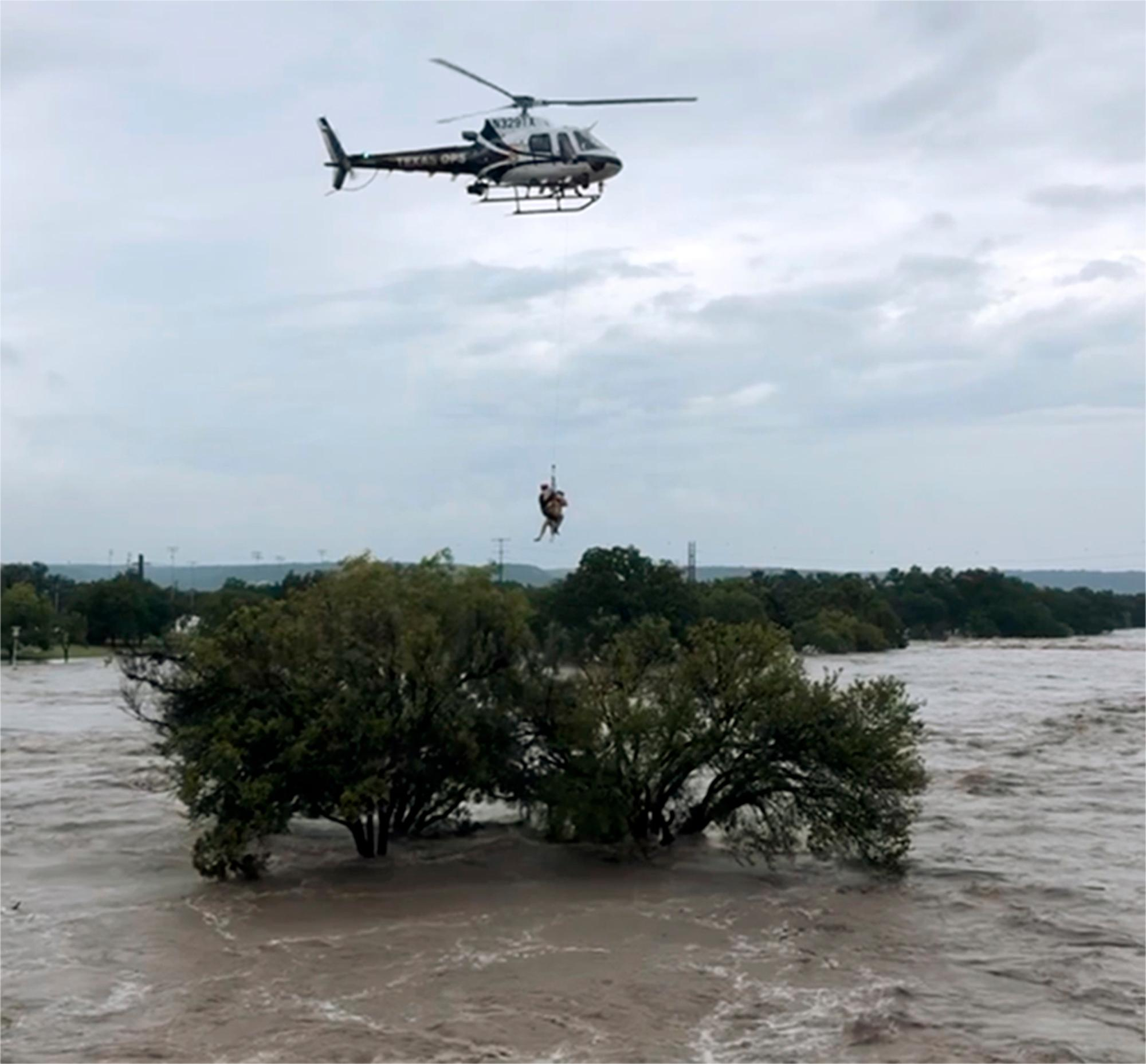 This photo from video provided by the Texas Parks and Wildlife Department shows a helicopter crew from the Texas Department of Public Safety performing a rescue from the South Llano River near Junction, Texas, on Monday, Oct. 8, 2018. (Texas Parks and Wildlife Department via AP)