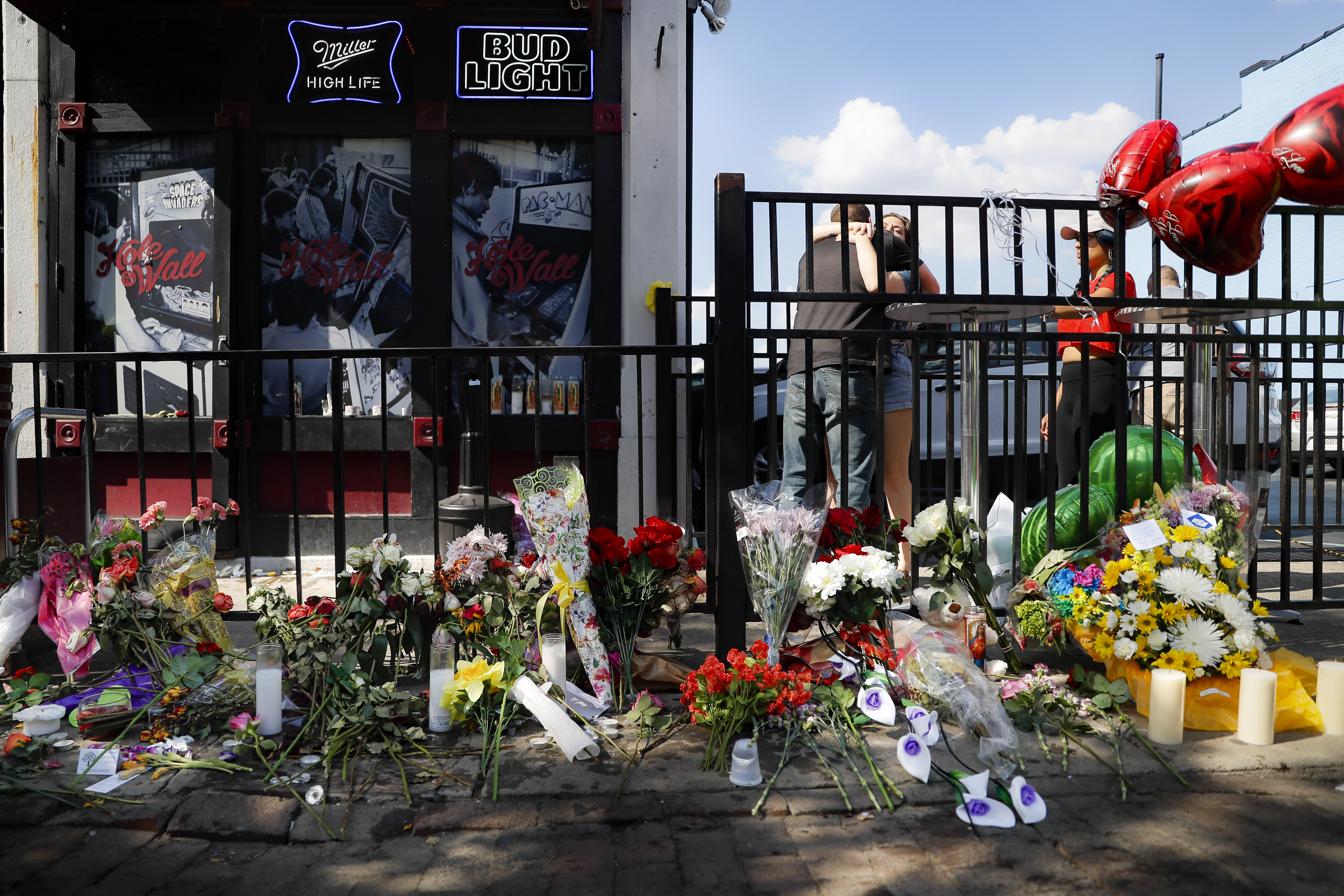 "Mourners embrace near a makeshift memorial outside the ""Hole in the Wall"" bar in the Oregon District, Monday, Aug. 5, 2019, in Dayton, Ohio. The area was the scene of a mass shooting the previous day. (AP Photo/John Minchillo)"