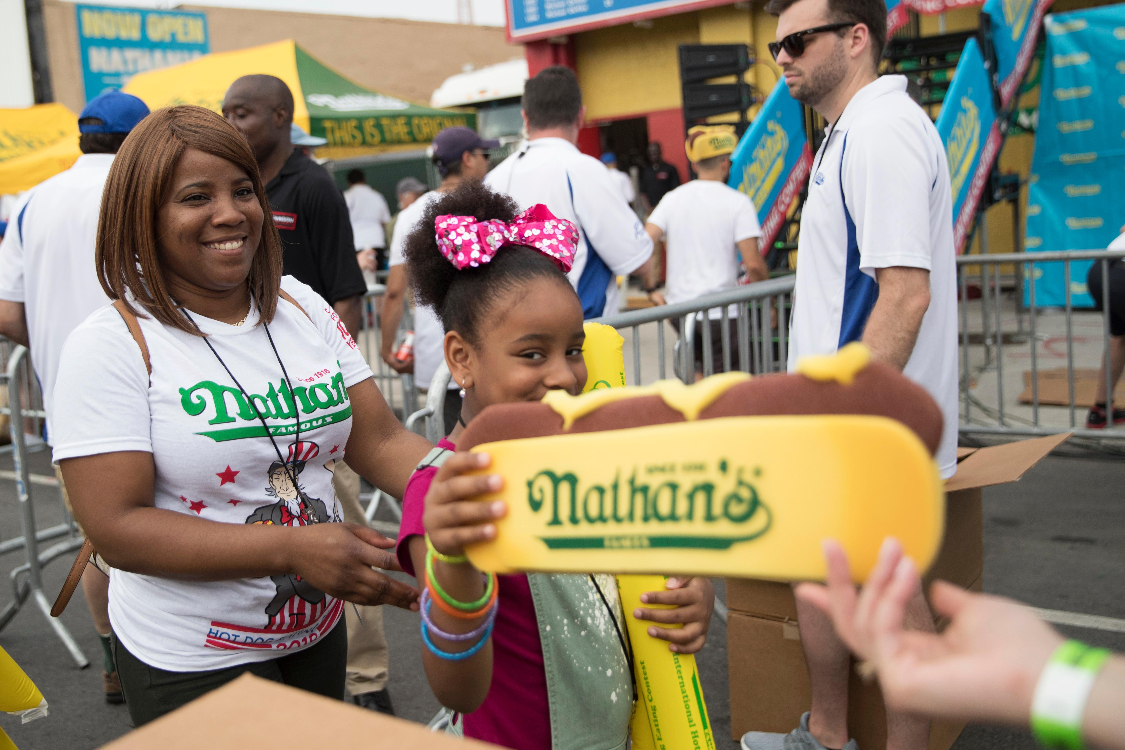Hot dog hats are distributed to the fans as the enter the Nathan's Famous Fourth of July hot dog eating contest, Wednesday, July 4, 2018, in New York's Coney Island. (AP Photo/Mary Altaffer)