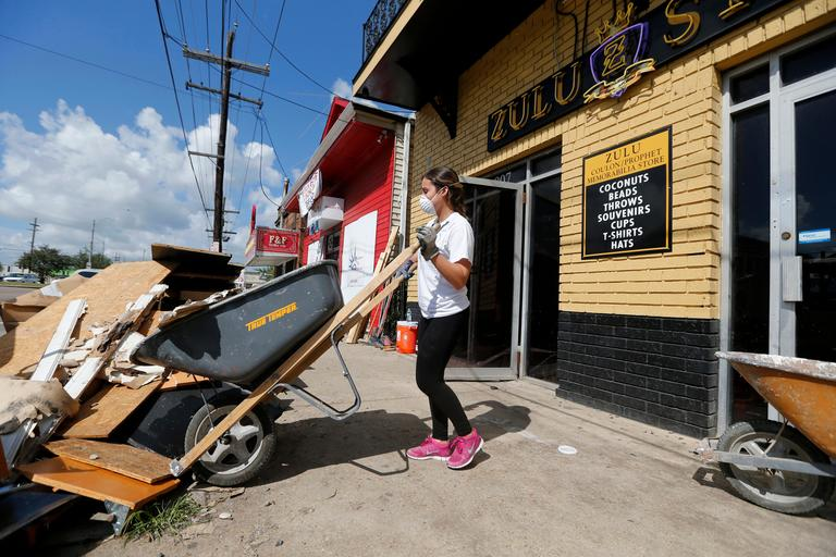 "FILE - In this Aug. 9, 2017 file photo, pre-med student Sheila Tendero, from the Miami Medical Team, helps gut the Zulu Social Aid & Pleasure Club Store, which flooded during rain storms this past weekend, in New Orleans. The city of New Orleans is perhaps one of the best examples of what President Donald Trump calls the country's ""crumbling infrastructure."" But city officials have raised doubts about whether the president's bold plan will help. New Orleans needs more than $11 billion to update key parts of its infrastructure, and currently has only about $2 billion in hand. (AP Photo/Gerald Herbert, File)"