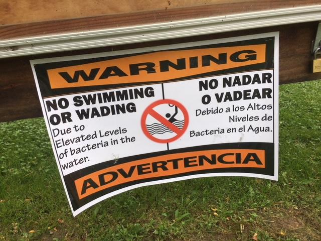 No Swimming signs were placed along the North Toe River when tests showed elevated levels of coliform and fecal bacteria after a 20,000 sewage leak on Tuesday. (Photo credit: WLOS Staff)