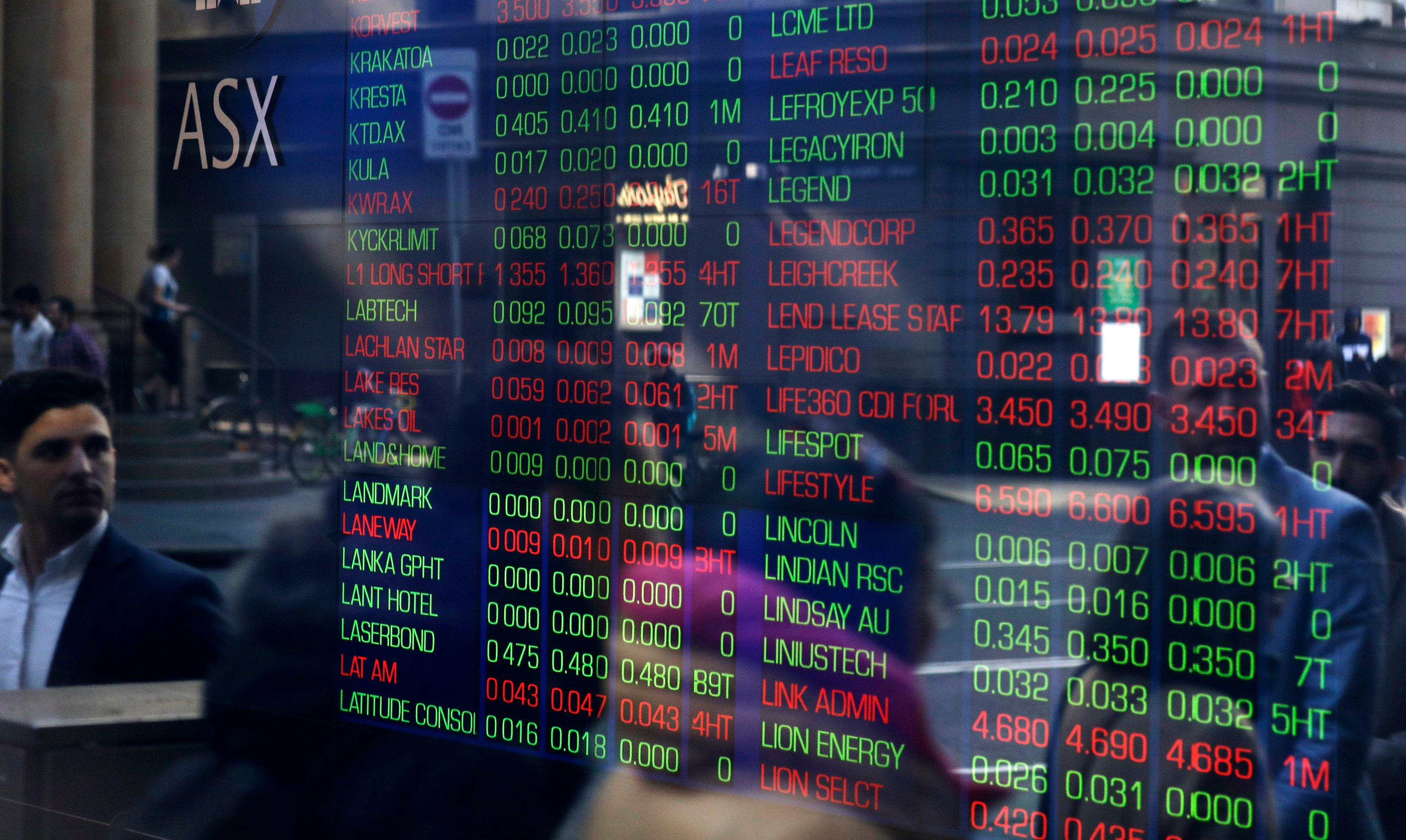 People are reflected in a window as they walk past the Australian Stock Exchange in Sydney, Thursday, Aug. 15, 2019. (AP Photo/Rick Rycroft)
