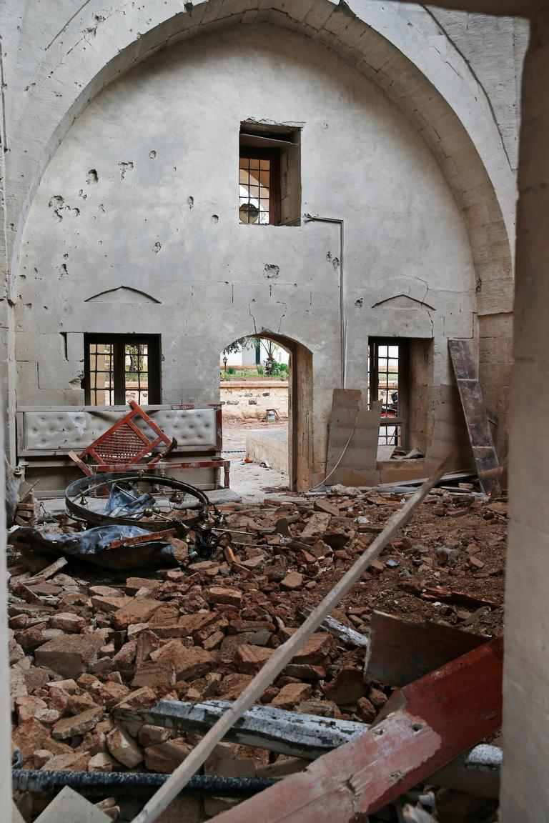 Debris is seen inside the Calik mosque damaged from a rocket attack Wednesday night, in the town of Kilis, Turkey, near the border with Syria, Thursday, Jan. 25, 2018, after two rockets fired from inside Syria wounded at least 13 people when they hit a house and the mosque during evening prayers. This is the latest in a series of rocket attacks against the Turkish border town since Ankara launched a military offensive into Afrin. (AP Photo/Lefteris Pitarakis)