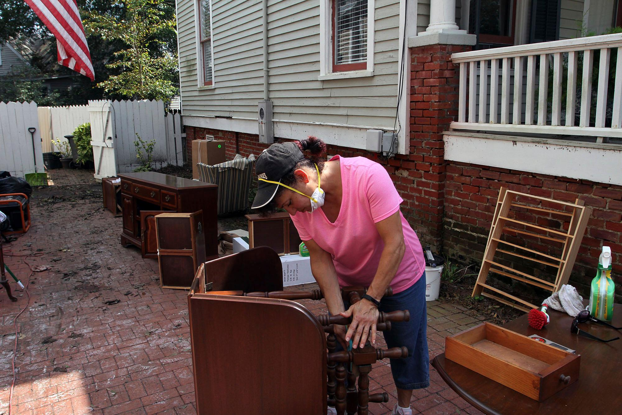 Volunteer Rita DeSanno helps clean furniture that was flooded at a home on Craven Street in New Bern, N.C., Thursday, Sept. 20, 2018. (Gray Whitley/Sun Journal via AP)