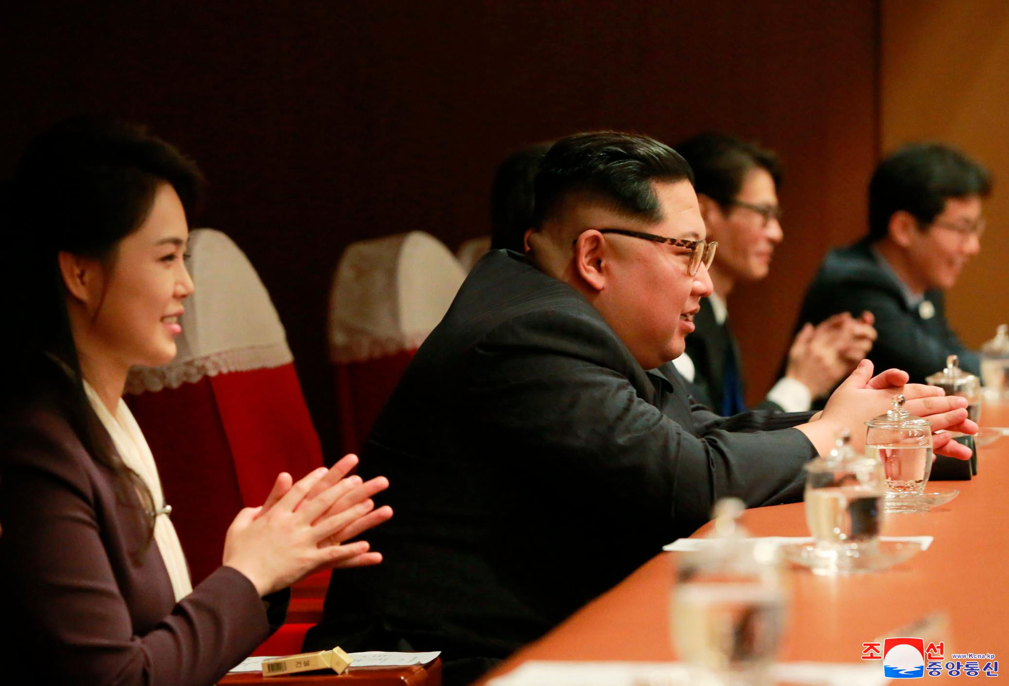 "In this photo provided by the North Korean government, North Korean leader Kim Jong Un, center right, and his wife Ri Sol Ju, left, sit on their seats during performance by members of a South Korean artistic group, including the South's pop legends and popular girl band Red Velvet, at East Pyongyang Grand Theater in Pyongyang, North Korea, Sunday, April 1, 2018. Kim clapped his hands as he, along with his wife and hundreds of other citizens, watched the rare performance Sunday by South Korean pop stars visiting Pyongyang, highlighting the thawing ties between the rivals after years of heightened tensions over the North's nuclear program. Independent journalists were not given access to cover the event depicted in this image distributed by the North Korean government. The content of this image is as provided and cannot be independently verified. Korean language watermark on image as provided by source reads: ""KCNA"" which is the abbreviation for Korean Central News Agency.  (Korean Central News Agency/Korea News Service via AP)"