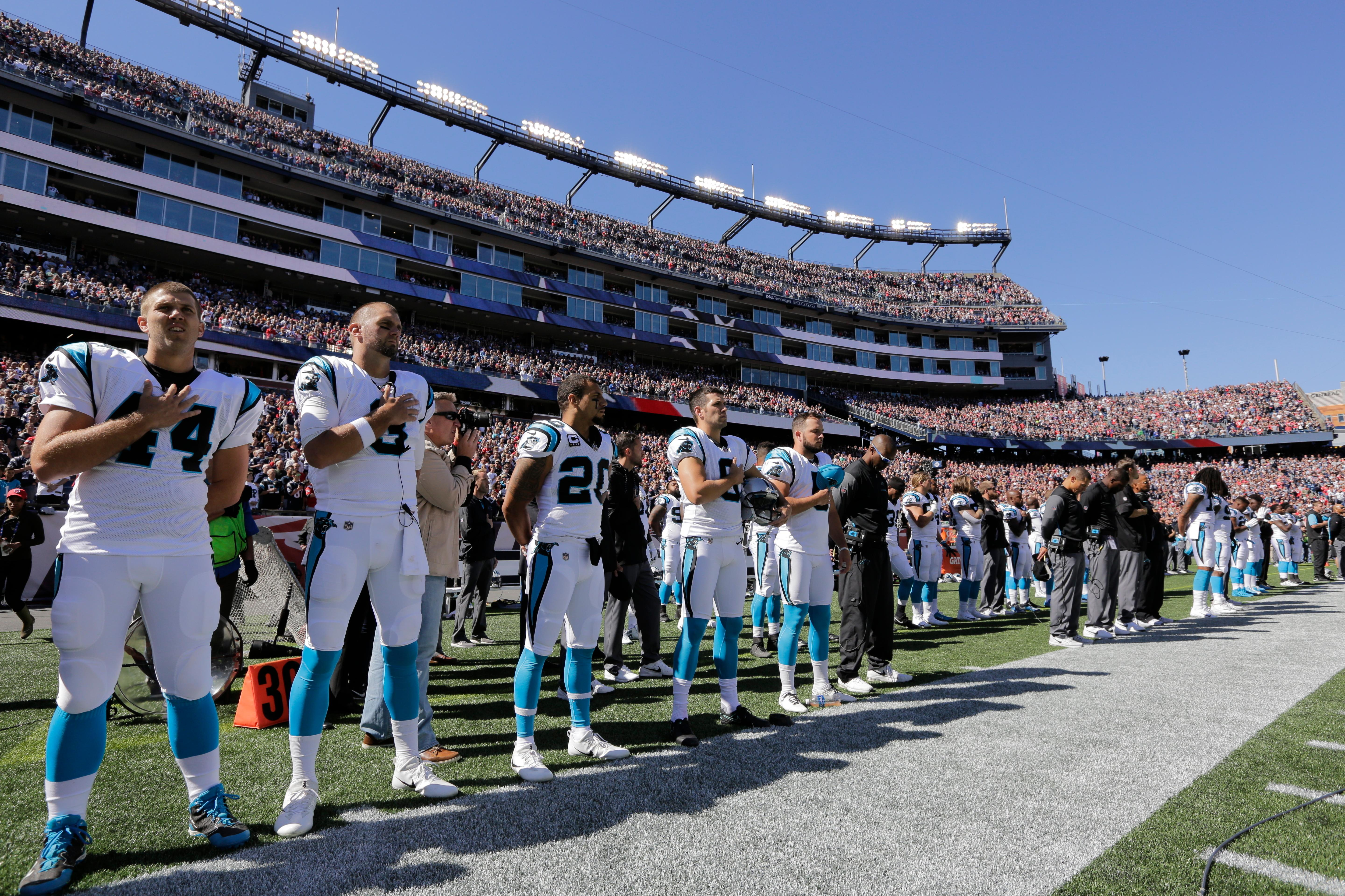 Members of the Carolina Panthers stand along the sideline during the national anthem before an NFL football game against the New England Patriots, Sunday, Oct. 1, 2017, in Foxborough, Mass. (AP Photo/Steven Senne)