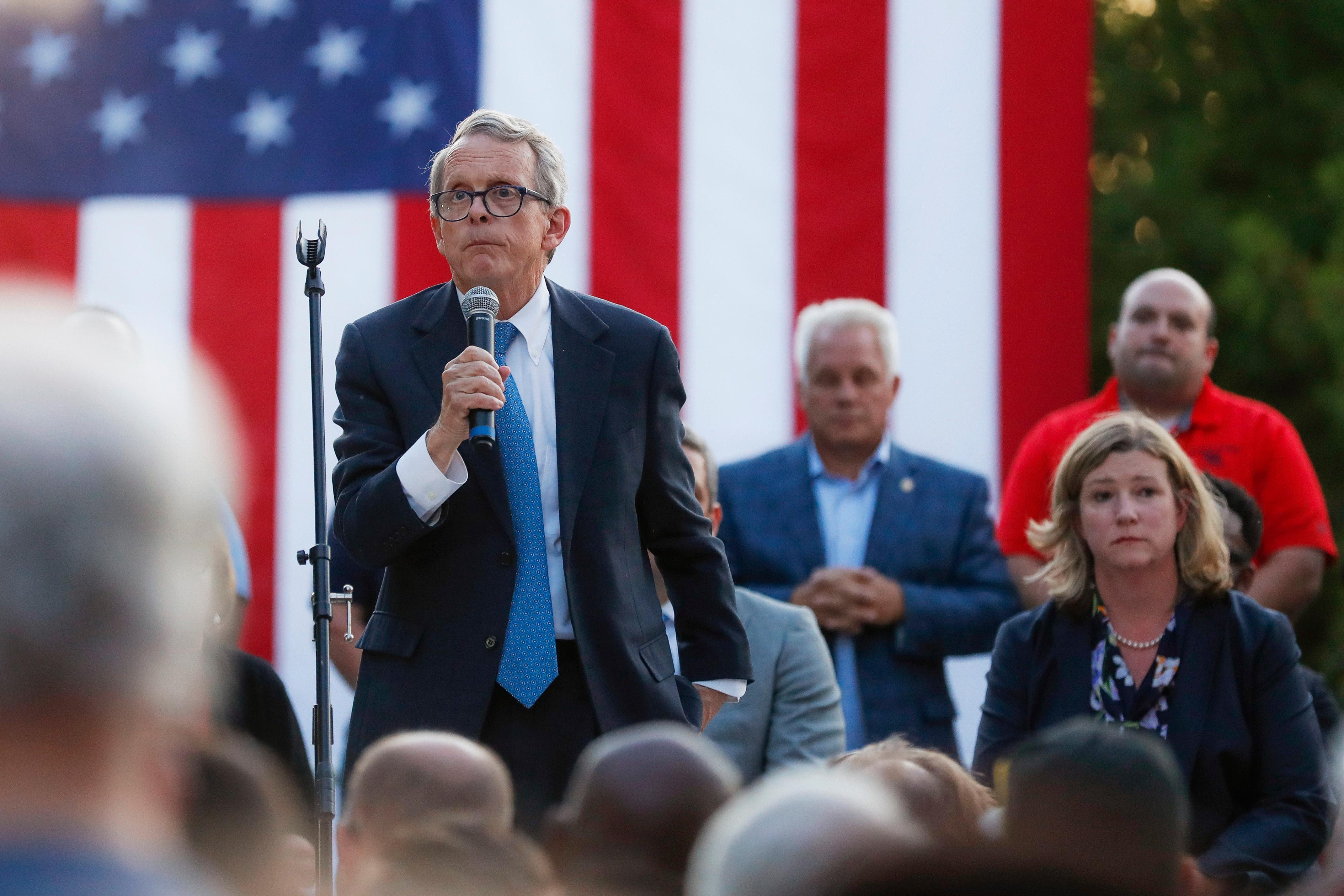 Ohio Gov. Mike DeWine, left, speaks alongside Dayton Mayor Nan Whaley, right, during a vigil at the scene of a mass shooting, Sunday, Aug. 4, 2019, in Dayton, Ohio. . (AP Photo/John Minchillo)