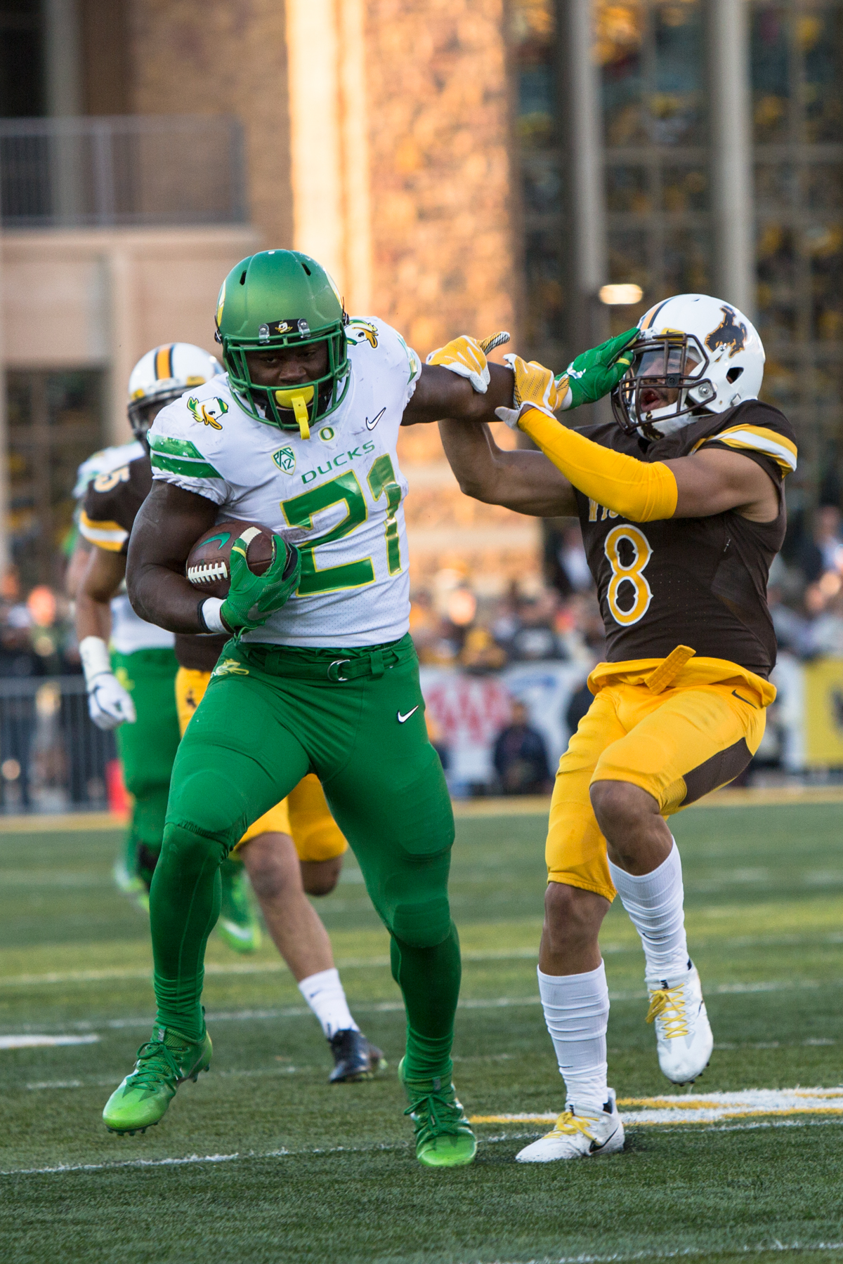 Oregon running back Royce Freeman (#21) stiff-arms Wyoming linebacker Jalen Ortiz (#8). The Oregon Ducks lead the Wyoming Cowboys 42 to 10 at the end of the first half on Saturday, September 16, 2017 in Laramie, Wyo. Photo by Austin Hicks, Oregon News Lab