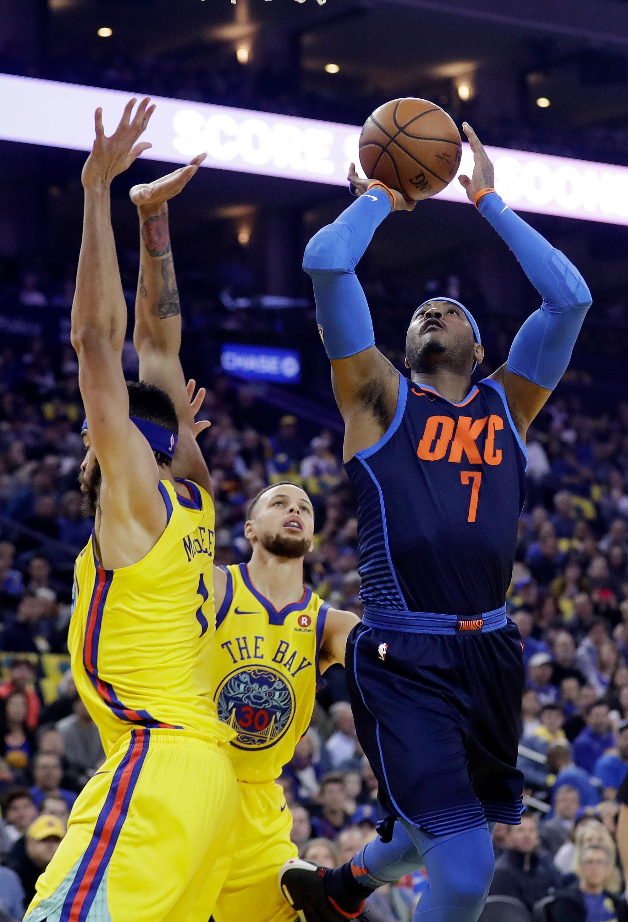 Oklahoma City Thunder's Carmelo Anthony (7) shoots next to Golden State Warriors' Stephen Curry, center, and JaVale McGee during the first half of an NBA basketball game Saturday, Feb. 24, 2018, in Oakland, Calif. (AP Photo/Marcio Jose Sanchez)