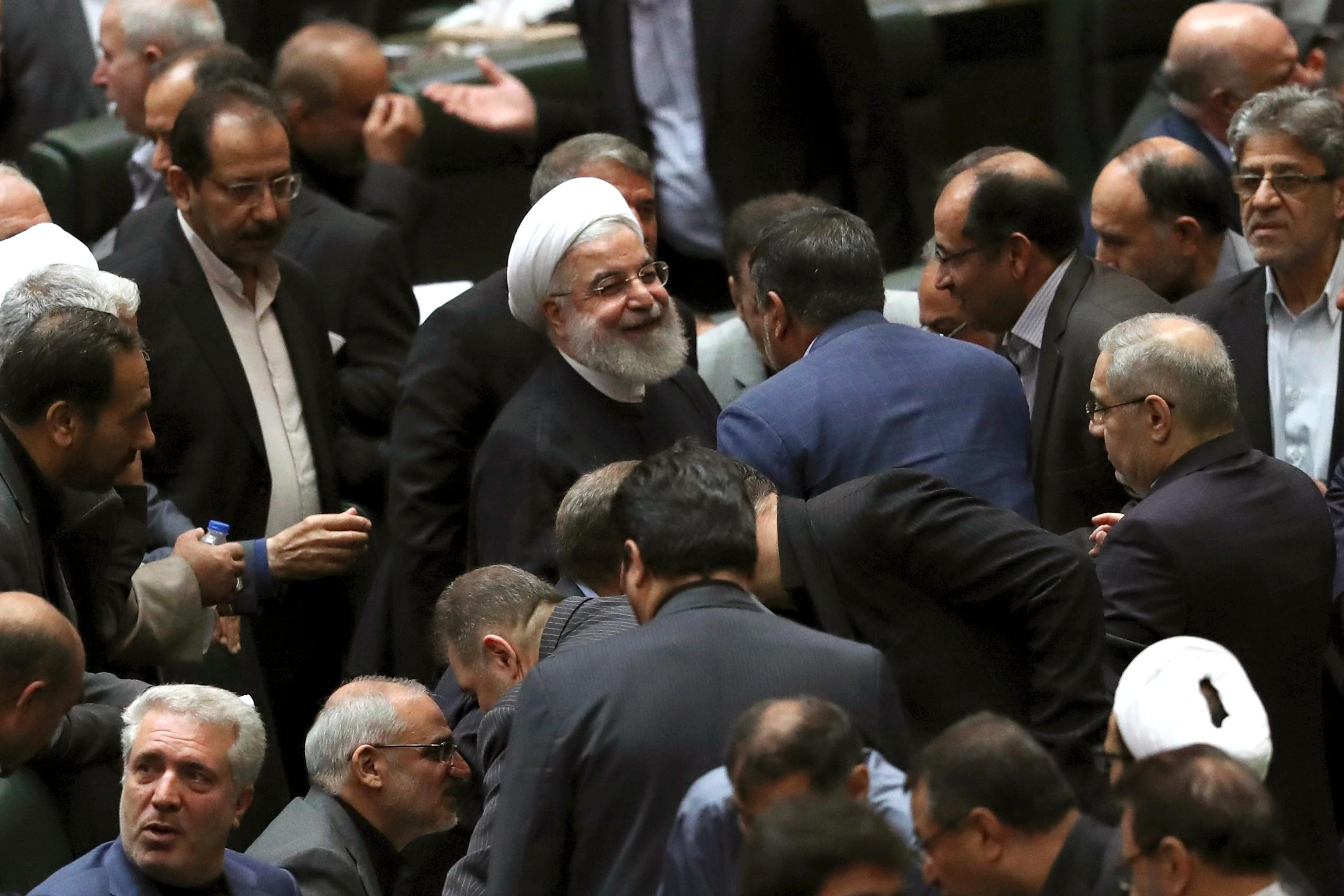 Iranian President Hassan Rouhani, center, listens to a lawmaker after defending his proposed tourism and education ministers, in Tehran, Iran, Tuesday, Sept. 3, 2019. (AP Photo/Vahid Salemi)