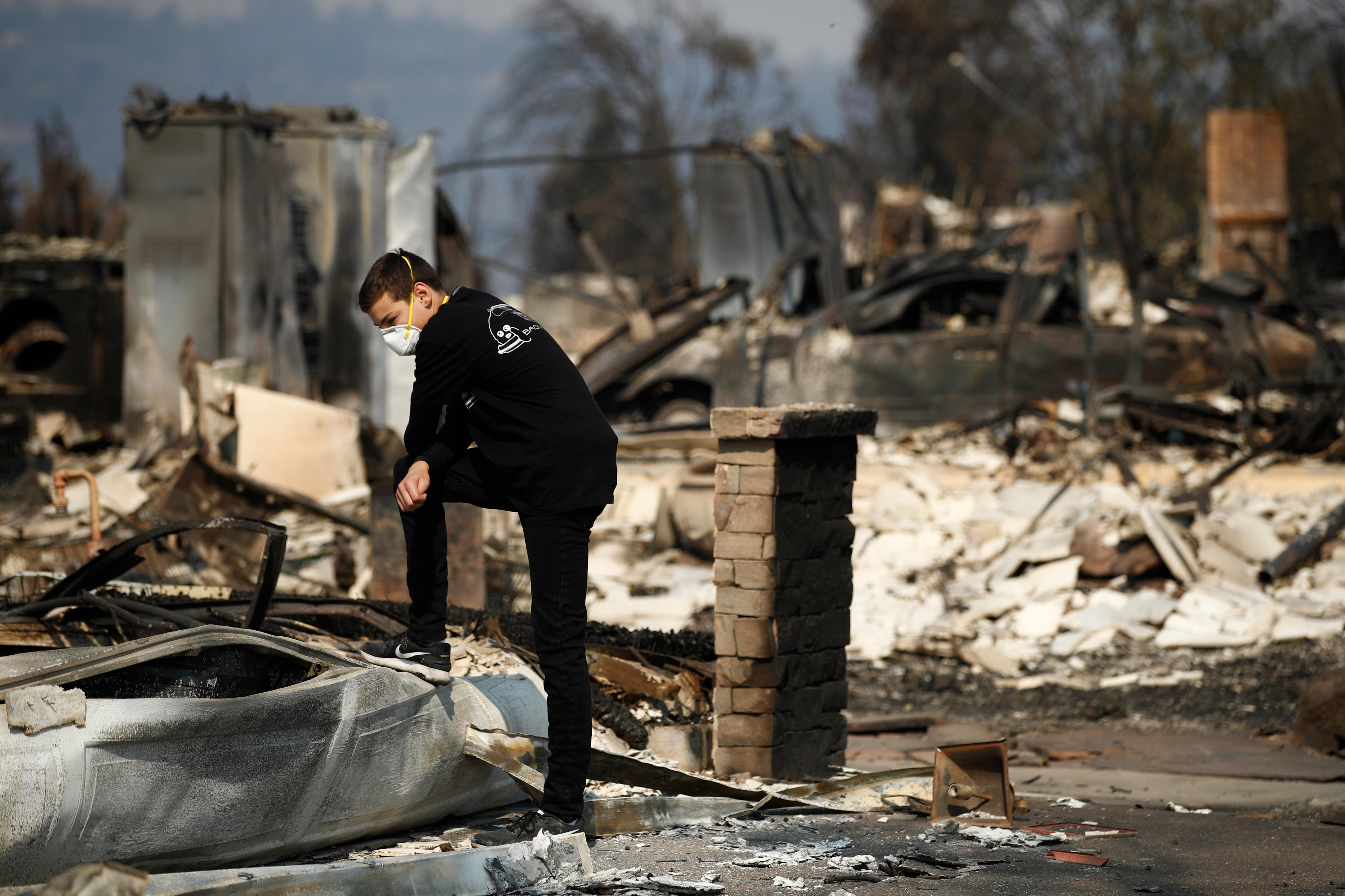 "Benjamin Lasker, 16, pauses while looking at what remains of his home after a wildfire swept through Sunday, Oct. 15, 2017, in Santa Rosa, Calif. With the winds dying down, fire officials said Sunday they have apparently ""turned a corner"" against the wildfires that have devastated California wine country and other parts of the state over the past week, and thousands of people got the all-clear to return home. (AP Photo/Jae C. Hong)"