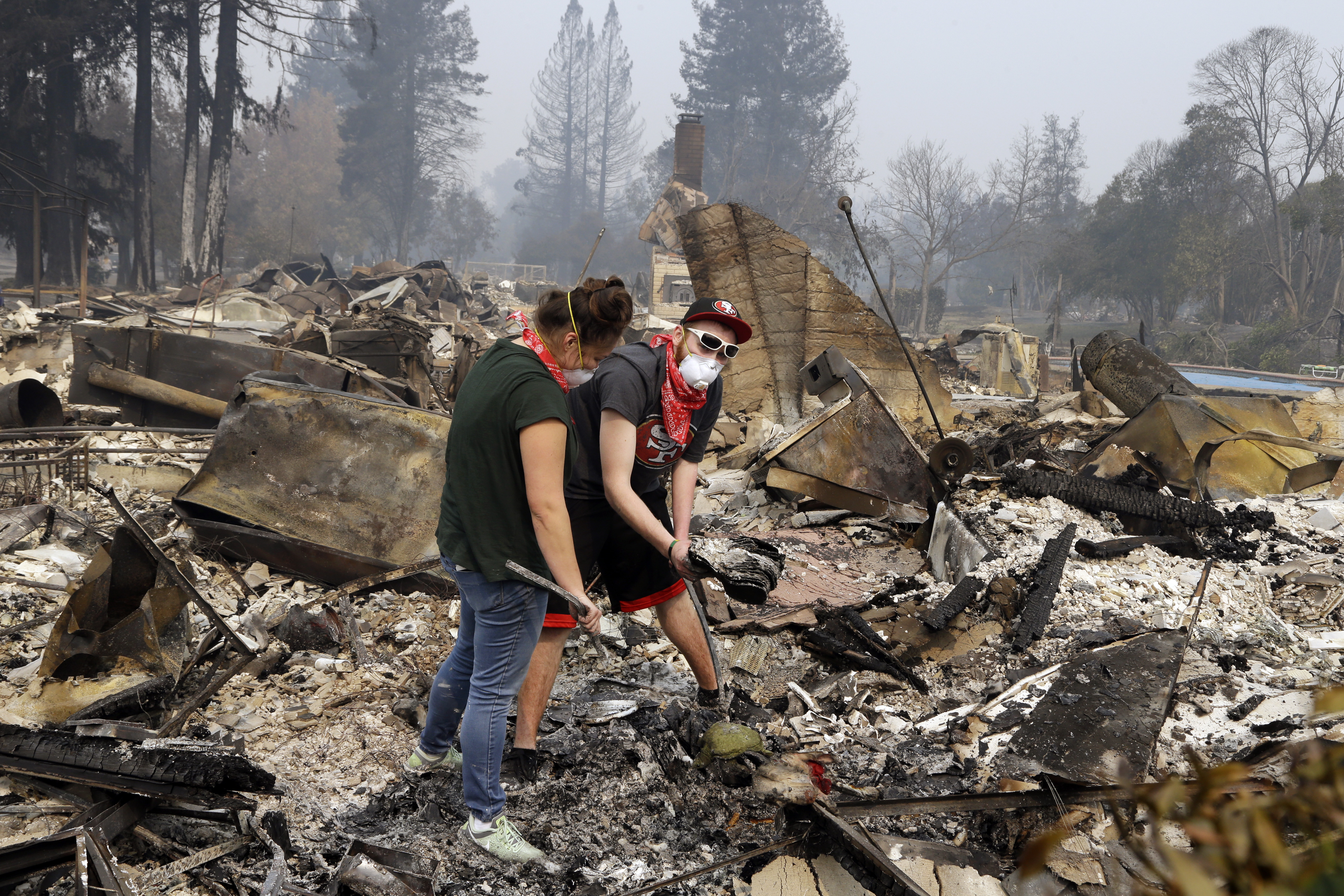 Robyn & Daniel Pellegrini search for belongings in the ashes of their home that was destroyed by fire in the Coffey Park area of Santa Rosa, Calif., on Tuesday, Oct. 10, 2017. An onslaught of wildfires across a wide swath of Northern California broke out almost simultaneously then grew exponentially, swallowing up properties from wineries to trailer parks and tearing through both tiny rural towns and urban subdivisions. (AP Photo/Ben Margot)
