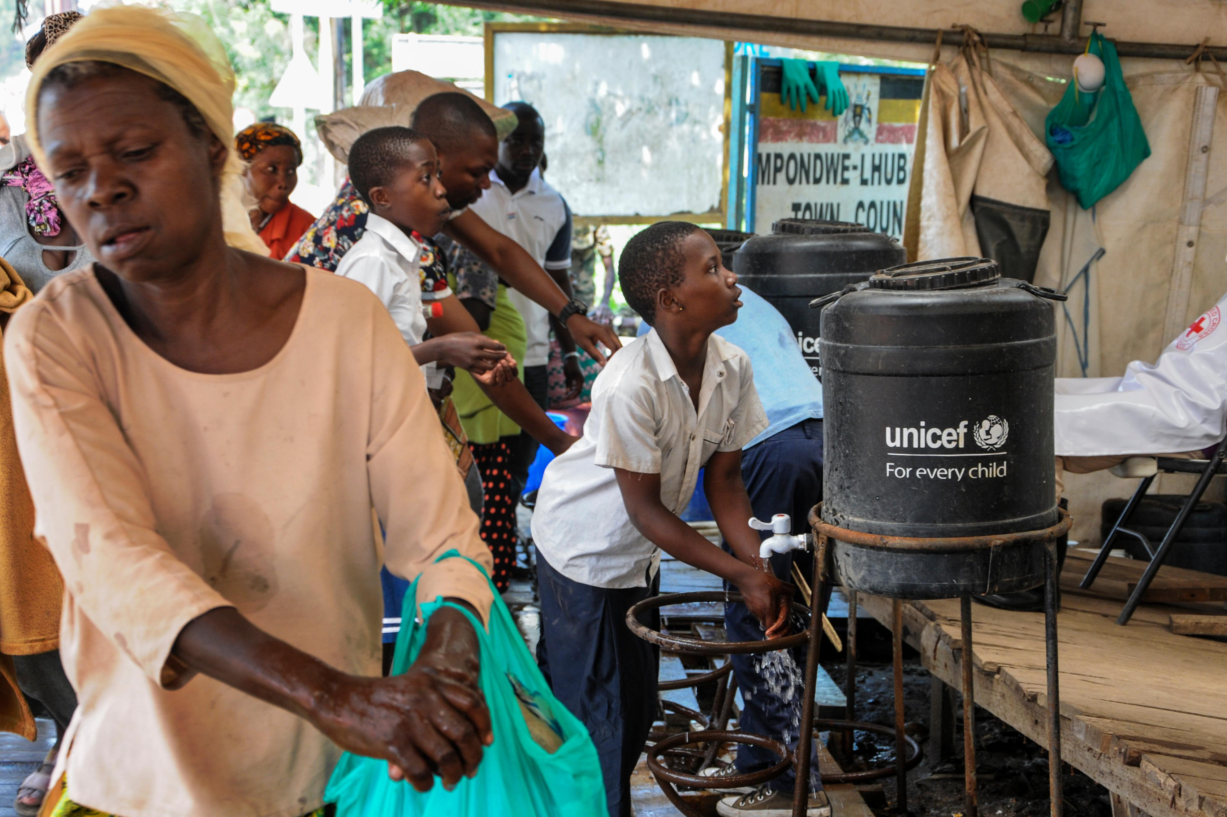 People coming from Congo wash their hands with chlorinated water to prevent the spread of infection, at the Mpondwe border crossing with Congo, in western Uganda Friday, June 14, 2019. (AP Photo/Ronald Kabuubi)