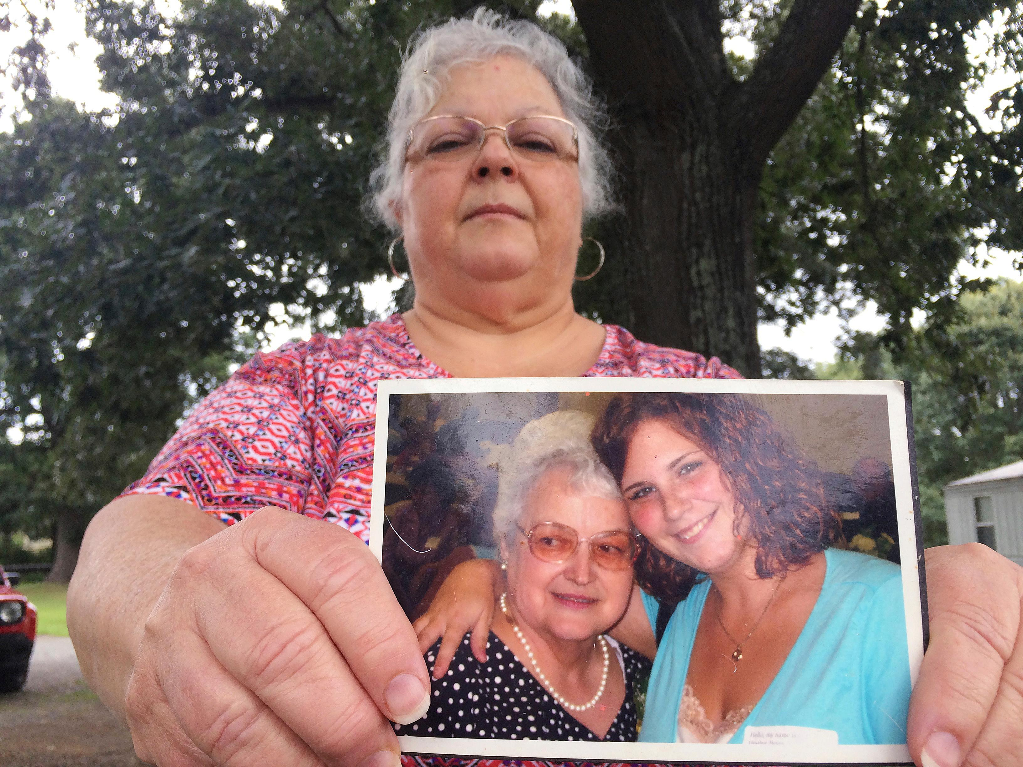 FILE- In this Aug. 14, 2017 file photo, Susan Bro, the mother of Heather Heyer, holds a photo of Bro's mother and her daughter.{ } (AP Photo/Joshua Replogle, File)