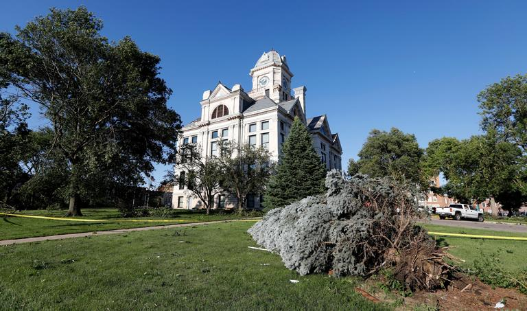 An uprooted tree lies in front of the tornado damaged Marshall County Courthouse, Thursday, July 19, 2018. (AP Photo/Charlie Neibergall)
