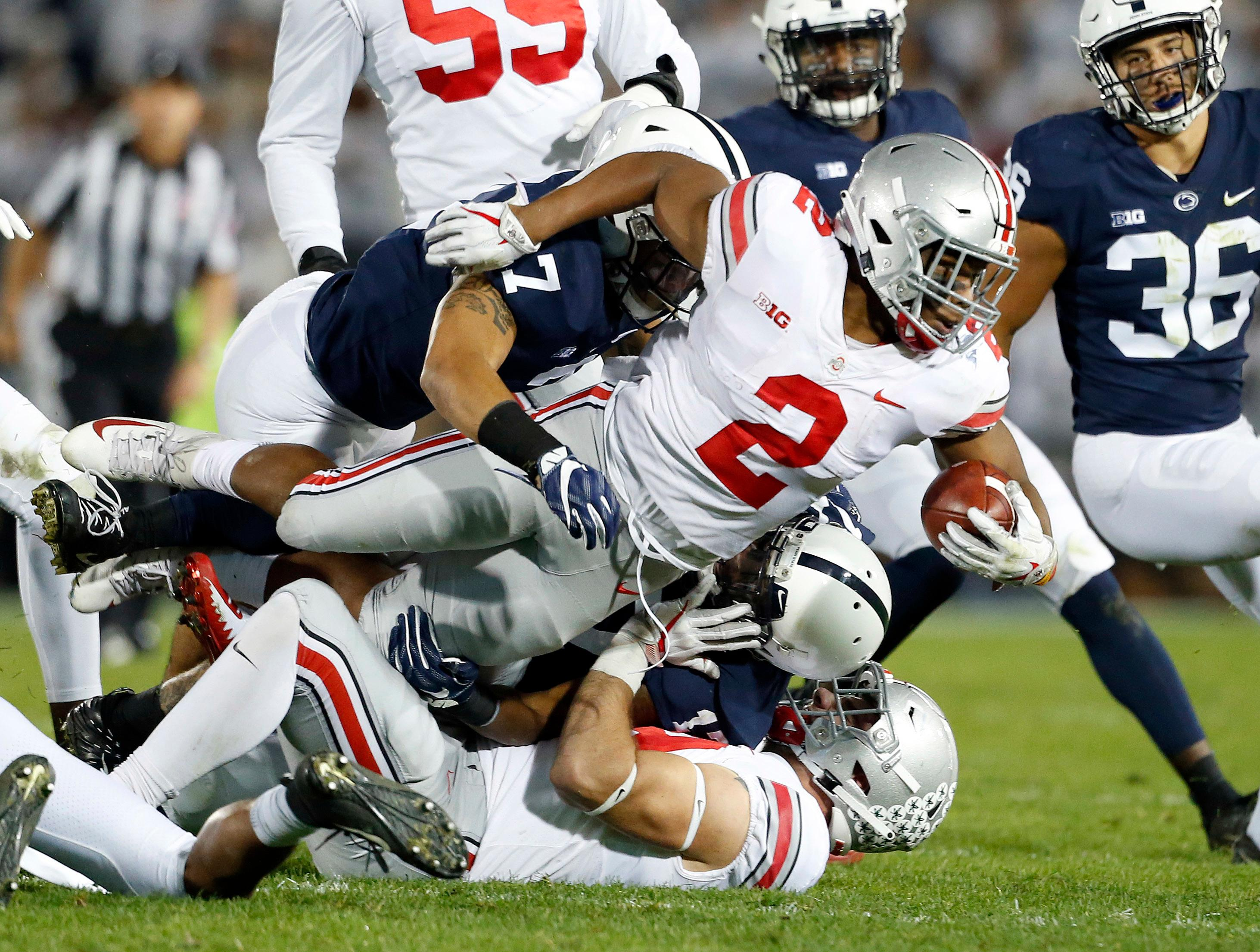 Ohio State's J.K. Dobbins (2) is tackled by Penn State's Koa Farmer (7) during the first half of an NCAA college football game in State College, Pa., Saturday, Sept. 29, 2018. (AP Photo/Chris Knight)