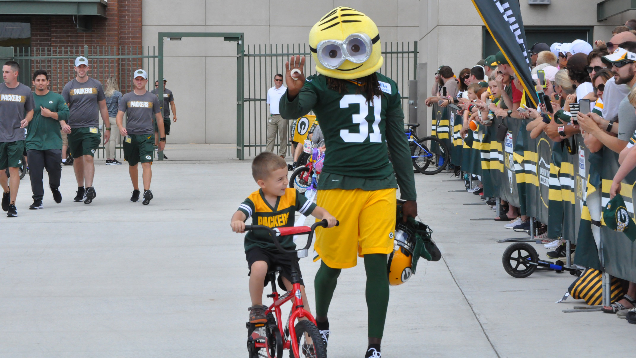 Green Bay Packers' Davon House (31) wears a Minion mask as he accompanies a child to training camp practice July 26, 2018. (WLUK/Sierra Trojan)