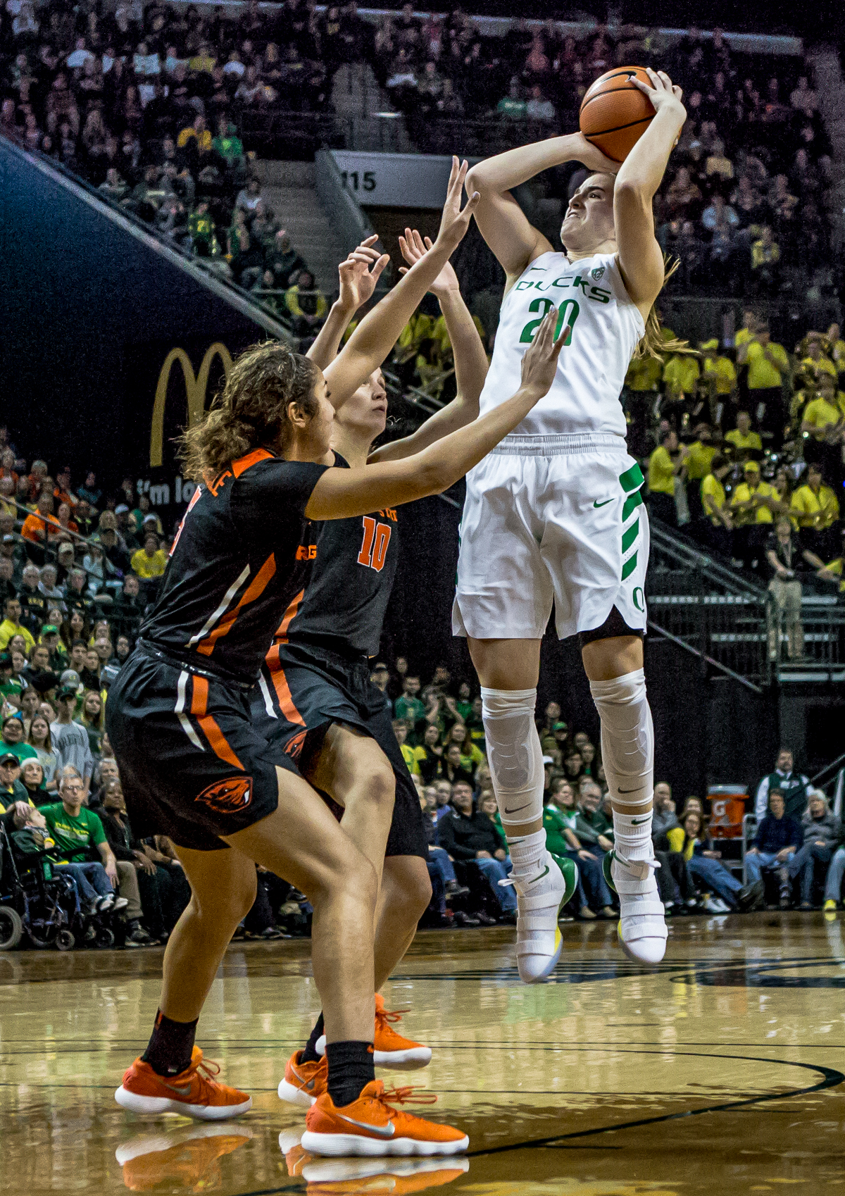 Oregon guard Sabrina Ionescu (#20) leaps to shoot over two Oregon State defenders. The Oregon Ducks defeated the Oregon State Beavers 75-63 on Sunday afternoon in front of a crowd of 7,249 at Matthew Knight Arena. The Ducks and Beavers split the two game Civil War with the Beavers defeating the Ducks on Friday night in Corvallis. The Ducks had four players in double digits: Satou Sabally with 21 points, Maite Cazorla with 16, Sabrina Ionescu with 15, and Mallory McGwire with 14. The Ducks shot 48.4% from the floor compared to the Beavers 37.3%. The Ducks are now 7-1 in conference play. Photo by Ben Lonergan, Oregon News Lab