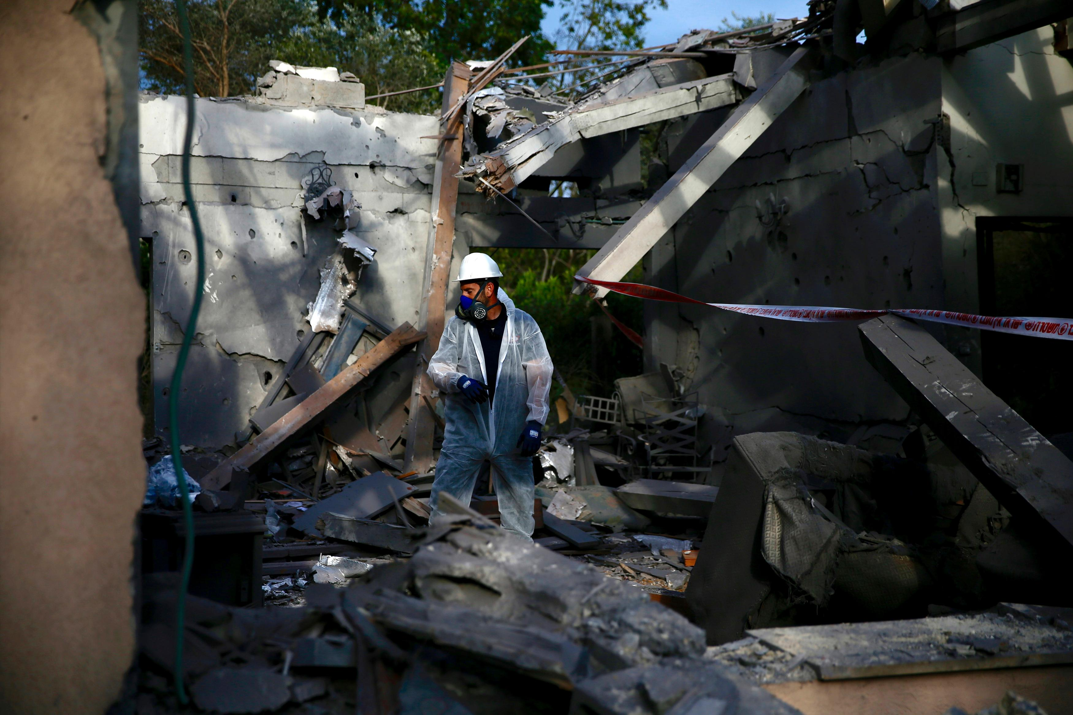 An Israeli police officer inspects the damage to a house hit by a rocket in Mishmeret, central Israel, Monday, March 25.{ } (AP Photo/Ariel Schalit)