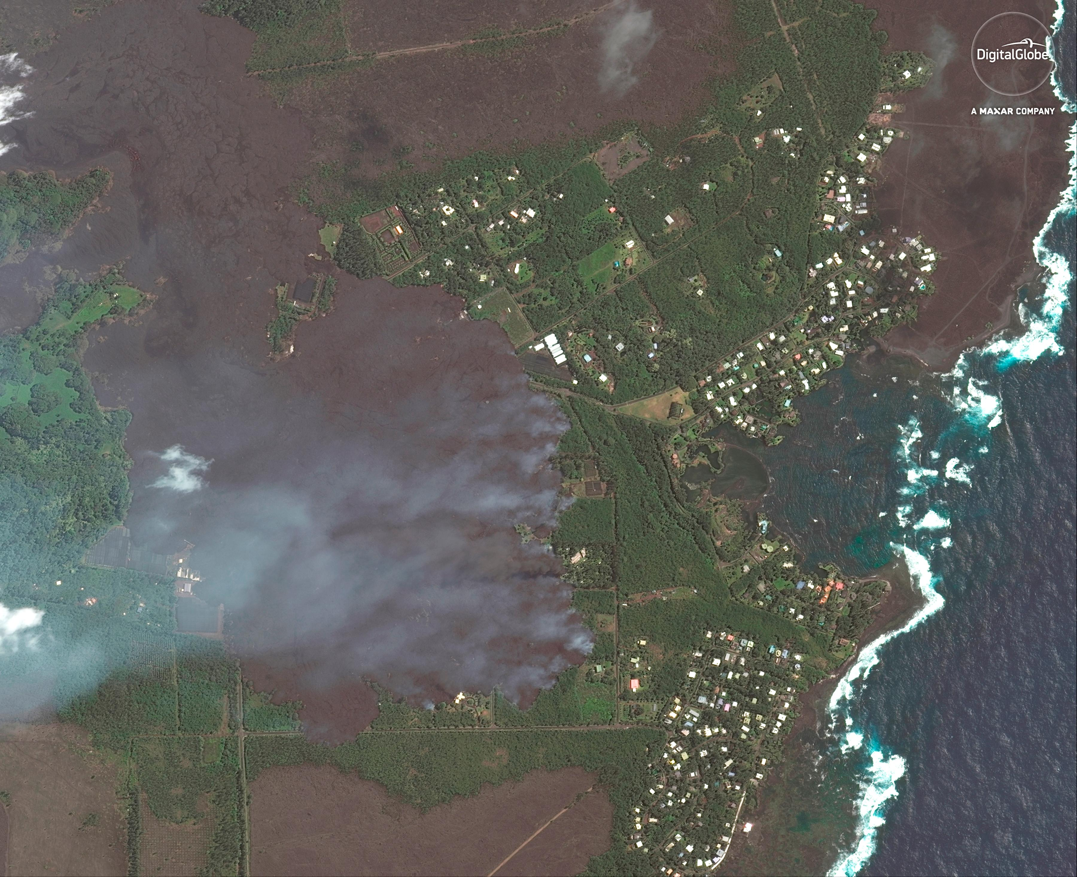 This satellite image provided by Digital Globe captured June 3, 2018, shows advancing lava flows on Hawaii as they approach Kapoho Bay and the Vacationland residential neighborhood.  Lava from the erupting Hawaii volcano has destroyed more than 100 homes in a rural Big Island district.  Hawaii County spokeswoman Janet Snyder says as of Monday, June 4, 2018, lava burned down 117 homes. Snyder says that's up from Friday's count of 87.  (Satellite Image ©2018 DigitalGlobe, a Maxar company via AP)