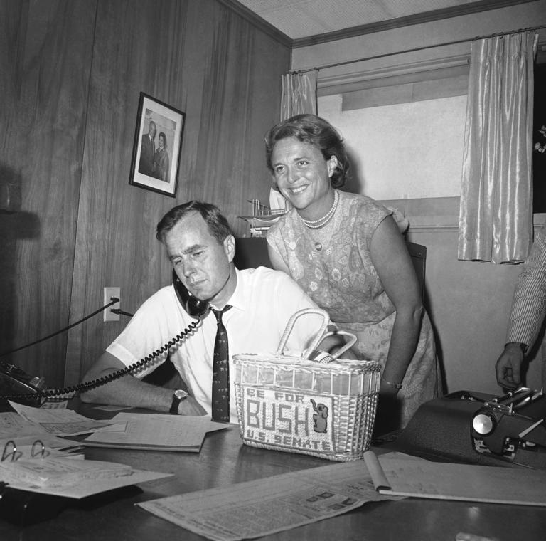 "FILE - In this June 6, 1964 file photo, George Bush, candidate for the Republican nomination for the U.S. Senate, gets returns by phone at his headquarters in Houston as his wife Barbara, beams her pleasure at the news. Former first couple George and Barbara Bush's relationship is a true love story, described by granddaughter Jenna Bush Hager as ""remarkable."" They met at a Christmas dance. She was 17. He was 18. Two years later they were married. Now 73 years later, with Barbara Bush declining further medical care for health problems, they are the longest-married couple in presidential history. (AP Photo/Ed Kolenovsky, File)"