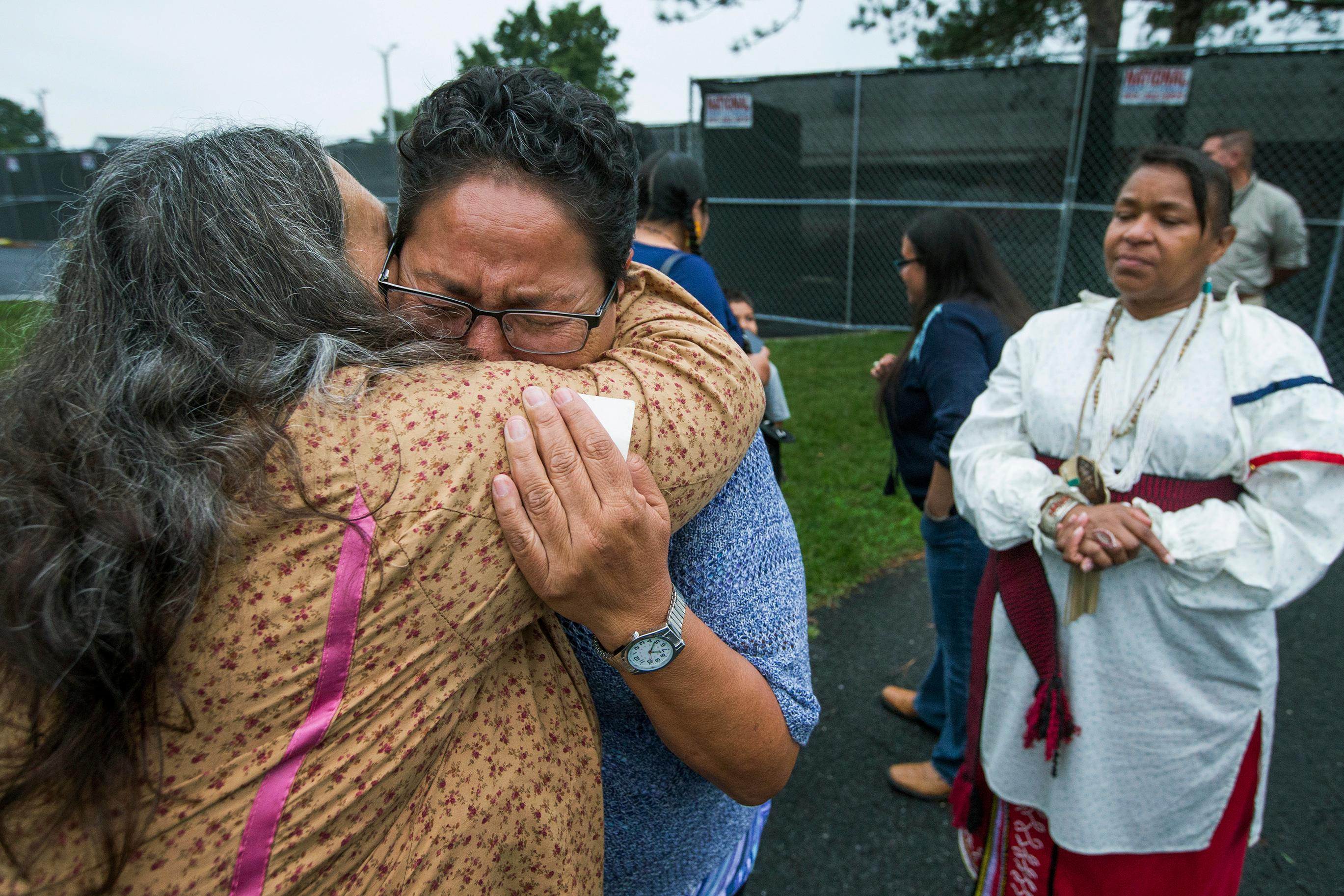 FILE - In this Monday, Aug. 7, 2017 file photo, Millie Friday, a descendent of Little Plume, a Native American student who was taken from his family and forced to go to boarding school, is comforted by Barbara Andrews-Christy of Circle Legacy Center, as Aílice Hall looks during a gathering on the grounds of the Carlisle Barracks, in Carlisle, Pa. (Charles Fox/The Philadelphia Inquirer via AP, File)