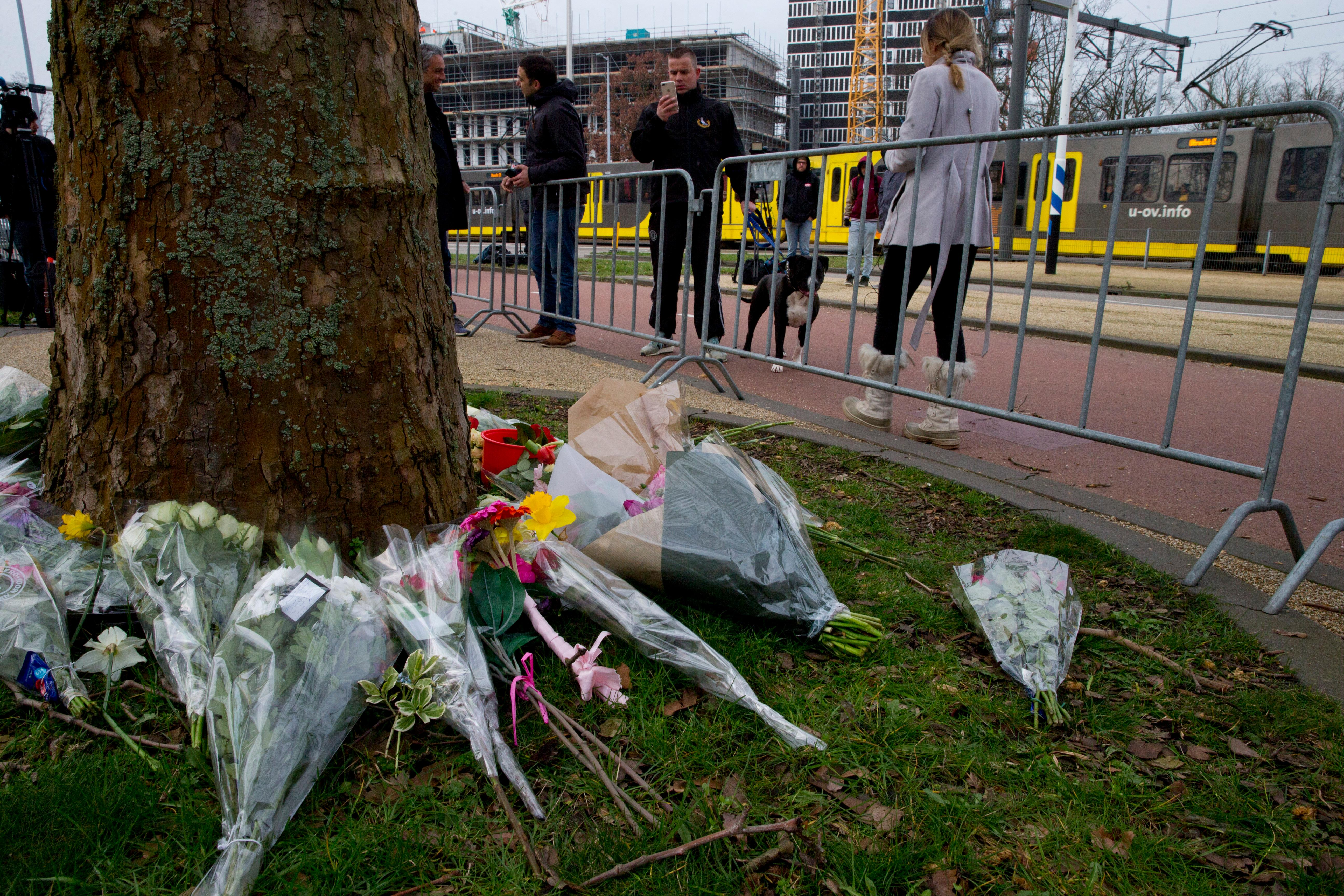 A tram passes in the background as flowers are seen in the foreground near the site of a shooting incident in a tram in Utrecht, Netherlands, Tuesday, March 19, 2019. (AP Photo/Peter Dejong)
