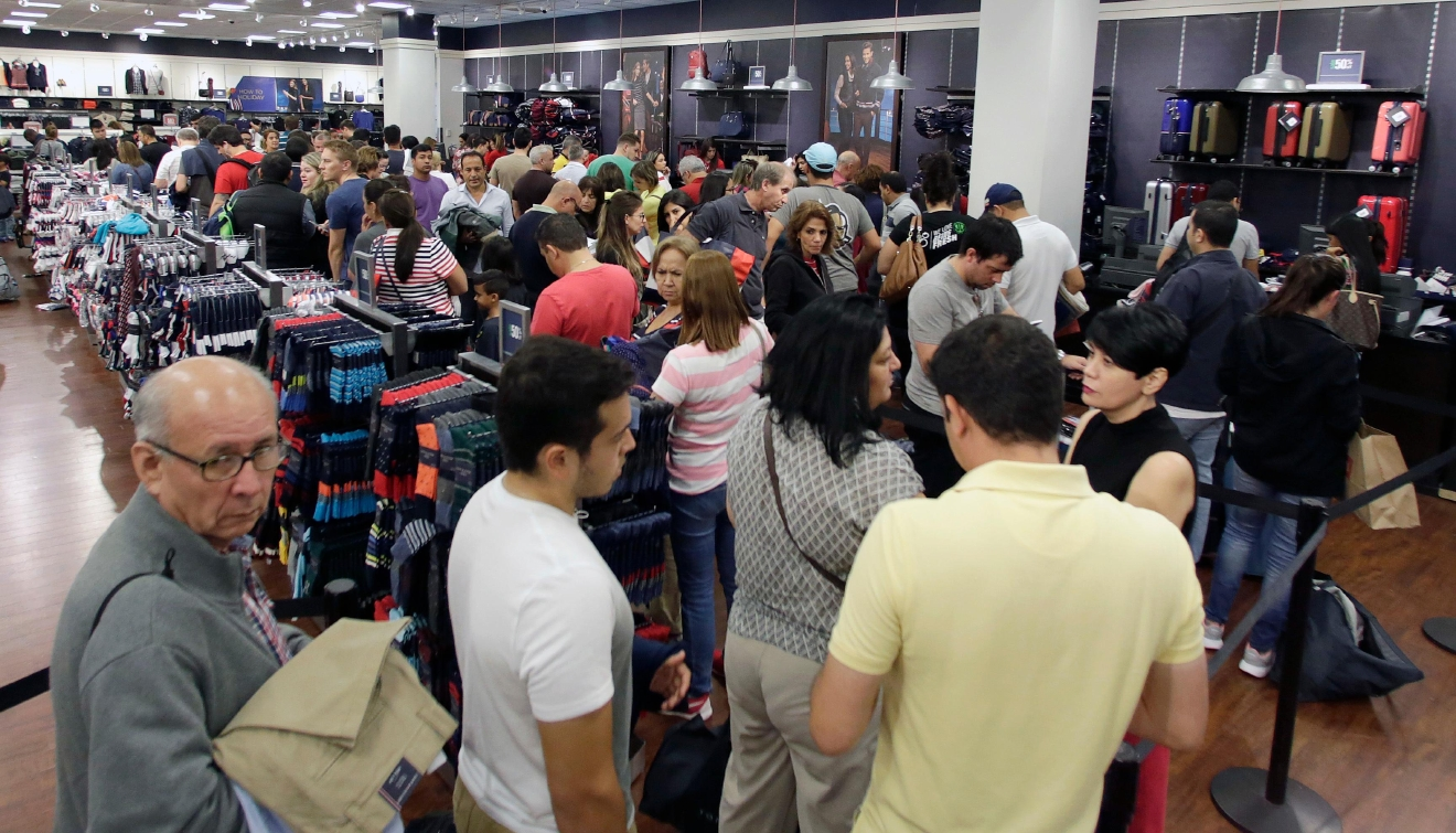 Shoppers stand in line to pay for their purchased merchandise at a Tommy Hilfiger store on Black Friday, Nov. 25, 2016, in Miami. (AP Photo/Alan Diaz)
