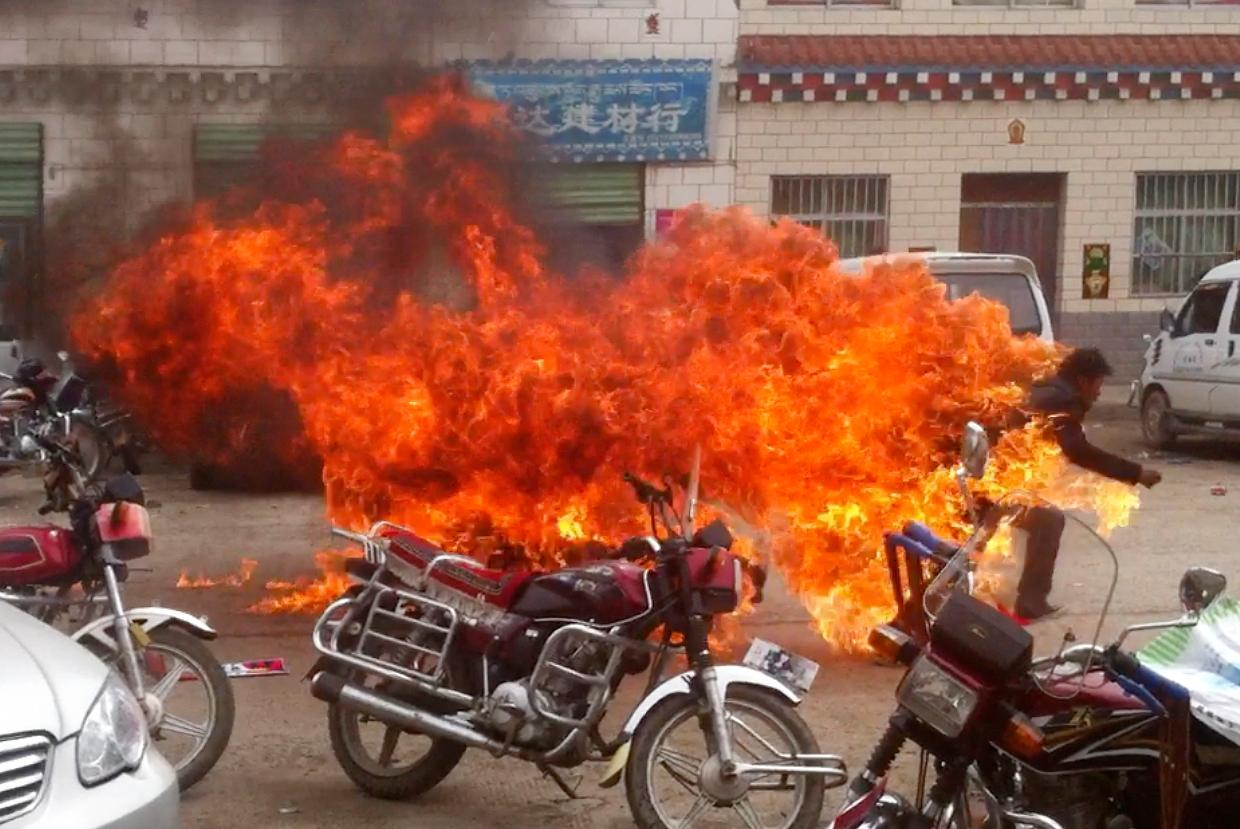 FILE - In this file image made from amateur video footage released by the Tibetan Youth Congress, a Tibetan runs in flames in his self-immolation to protest against Chinese rule, on a street in Yushu prefecture in China's Qinghai province Wednesday, June 20, 2012.{ } (The Tibetan Youth Congress via AP, File)