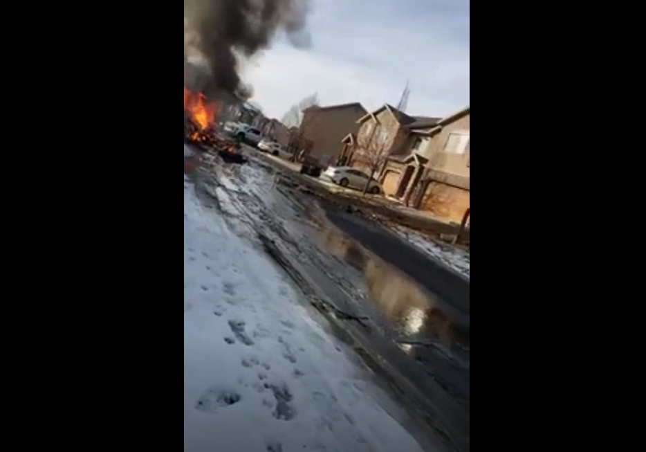 A small plane crashed in a neighborhood in Roy on Wednesday afternoon, clipping the roof of a home before it impacted the ground. (Screengrab from video courtesy Neal Randall)