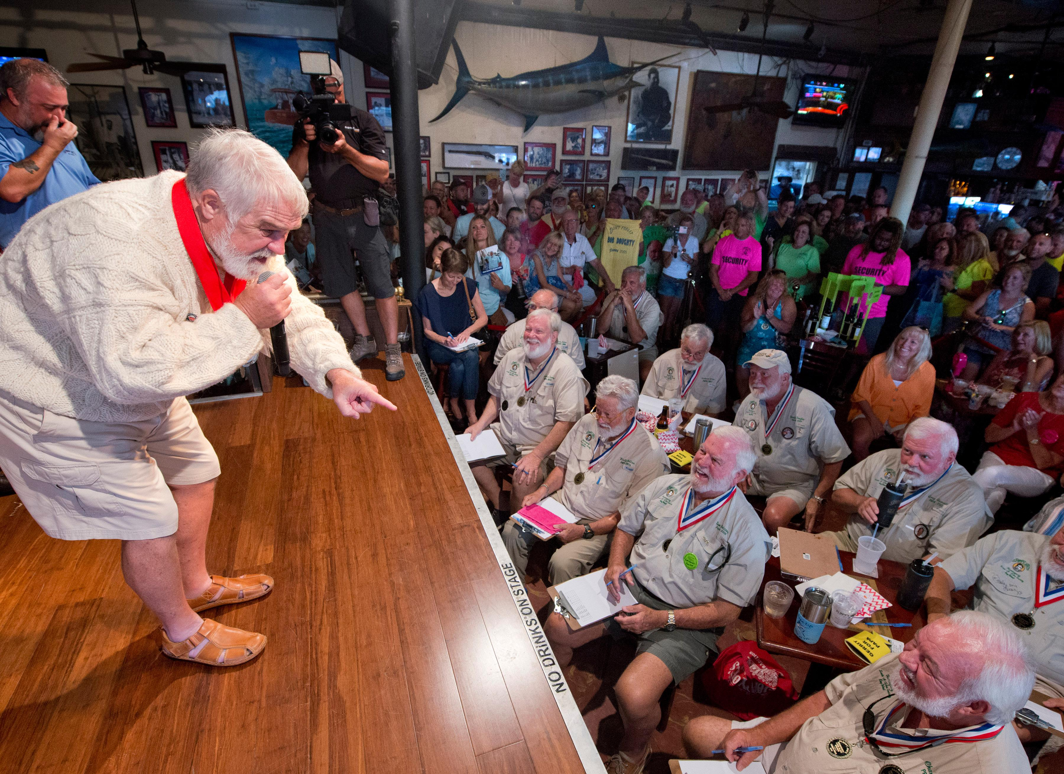 In this Saturday, July 20, 2019, photo provided by the Florida Keys News Bureau, Joe Maxey, left, implores past winners of the Hemingway Look-Alike Contest to judge him the winner of the 2019 competition at Sloppy Joe's Bar in Key West, Fla. Maxey went on to beat 141 other contestants to win. The competition highlighted activities during the yearly Hemingway Days festival that honors author Ernest Hemingway, who lived in Key West during the 1930s. (Andy Newman/Florida Keys News Bureau via AP)