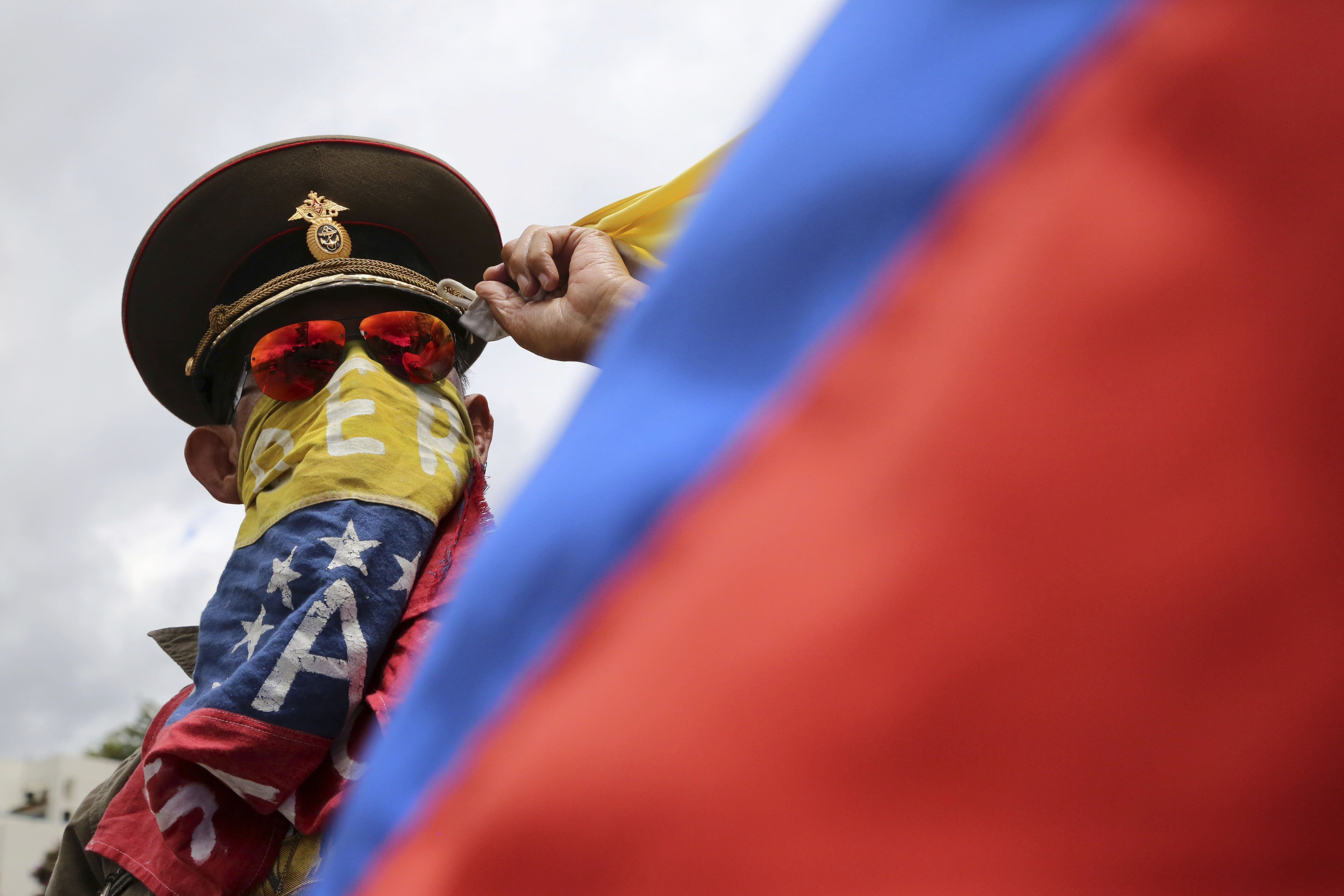 "In this Sunday, Aug. 6, 2017 photo, an anti-government demonstrator wearing a Russian military hat protests the government of Venezuela's President Nicolas Maduro in Caracas, Venezuela. Venezuelan ruling party chief Diosdado Cabello said the military squashed a ""terrorist"" attack at a military base on Sunday, shortly after a small group of men dressed in military fatigues released a video declaring themselves in rebellion. (AP Photo/Wil Riera)"