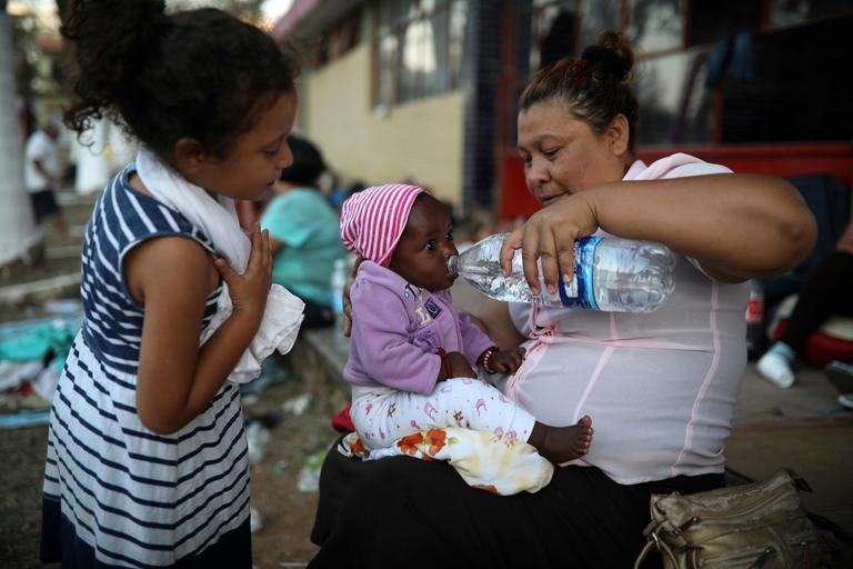 A Central American migrant woman gives water to a baby as the annual Migrant Stations of the Cross caravan sets up camp for a few days at a sports center in Matias Romero, Oaxaca state, Mexico, late Monday, April 2, 2018.{ } (AP Photo/Felix Marquez)