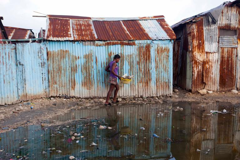 A woman skirts a puddle as she walks home in the seaside slum of Port-au-Prince, Haiti, Wednesday, Sept. 6, 2017. Heavy rain and 185-mph winds lashed the Virgin Islands and Puerto Rico's northeast coast Wednesday as Hurricane Irma roared through Caribbean islands. The northern parts of the Dominican Republic and Haiti could see 10 inches of rain. (AP Photo/Dieu Nalio Chery)