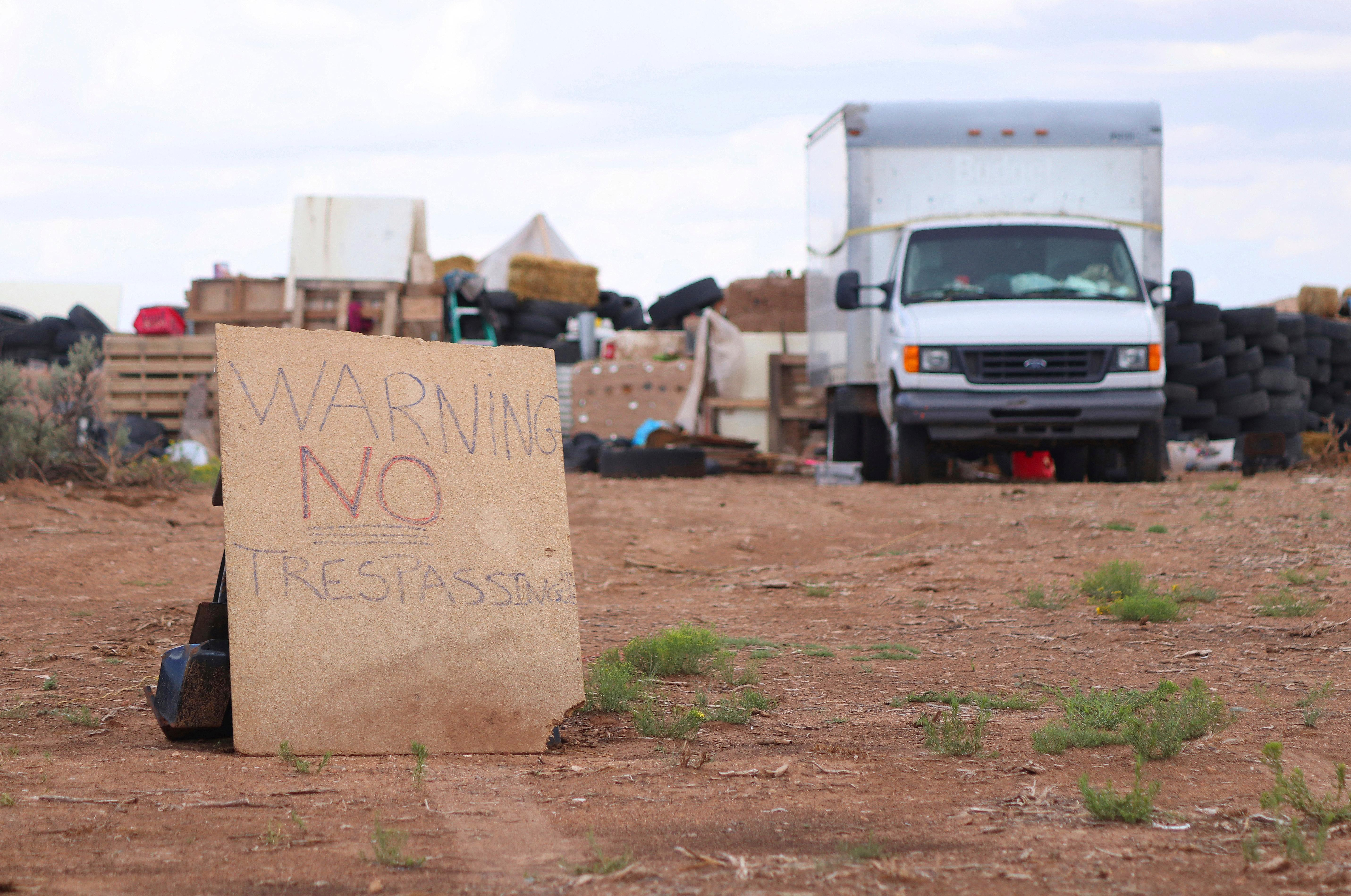 "This Aug. 5, 2018 photo shows a ""no trespassing"" sign outside the location where people camped near Amalia, N.M. Three women believed to be the mothers of 11 children found hungry and living in a filthy makeshift compound in rural northern New Mexico have been arrested, following the weekend arrests of two men, authorities said Monday, Aug. 6. (Jesse Moya/Santa Fe New Mexican via AP)"