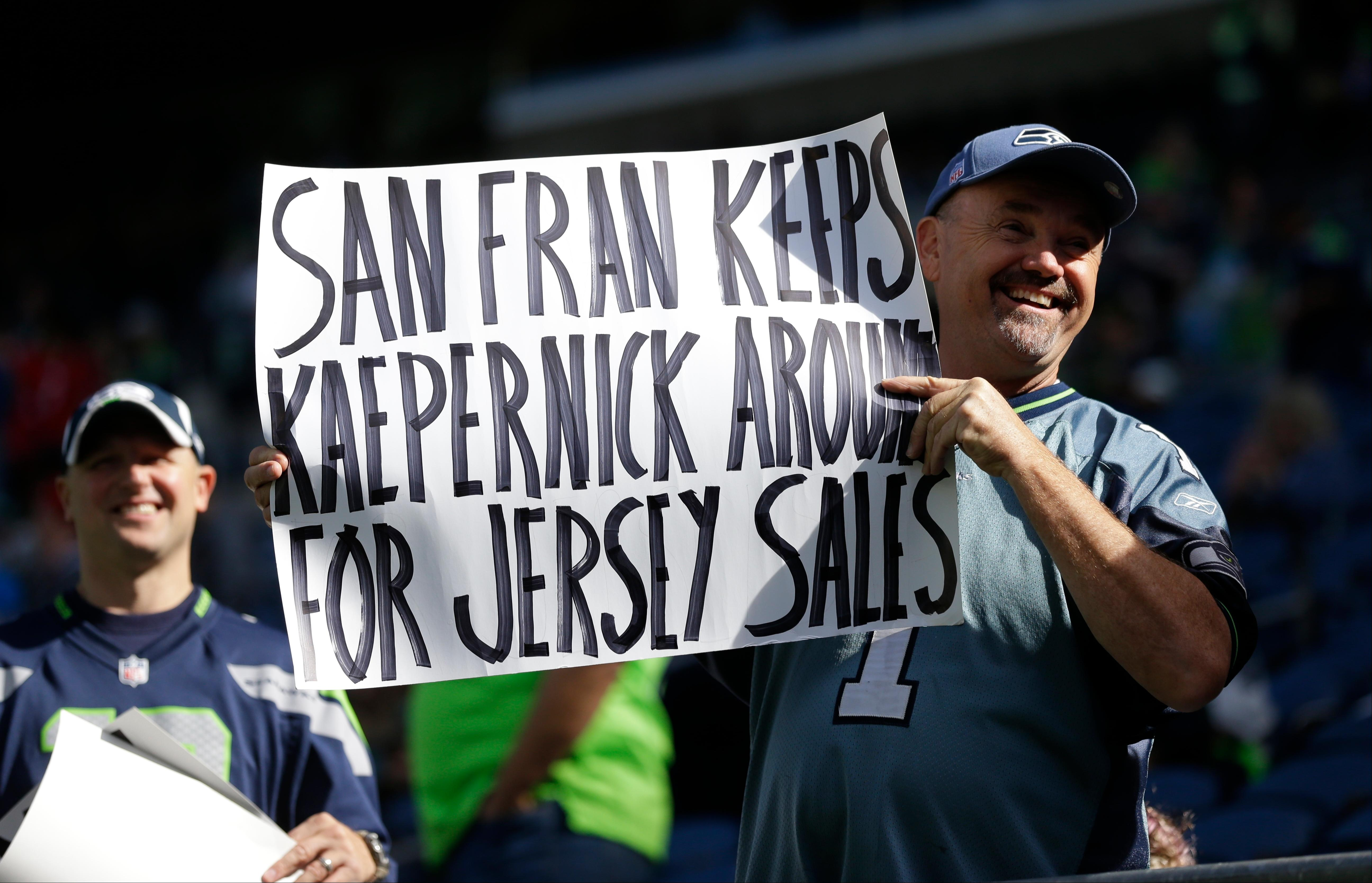 FILE - In this Sept. 25, 2016, file photo, a Seattle Seahawks fan holds up a sign about San Francisco 49ers' Colin Kaepernick before an NFL football game in Seattle. The once-rising star and Super Bowl quarterback has been unemployed since March, when he opted out of his contract and became a free agent who could sign with any team. Just weeks away from the regular season, he has become a symbol of the clash of celebrity, sports and social issues as more people, including players, fans, politicians, team owners and pundits, invoke his name to debate thorny issues of patriotism and race. (AP Photo/Ted S. Warren, File)