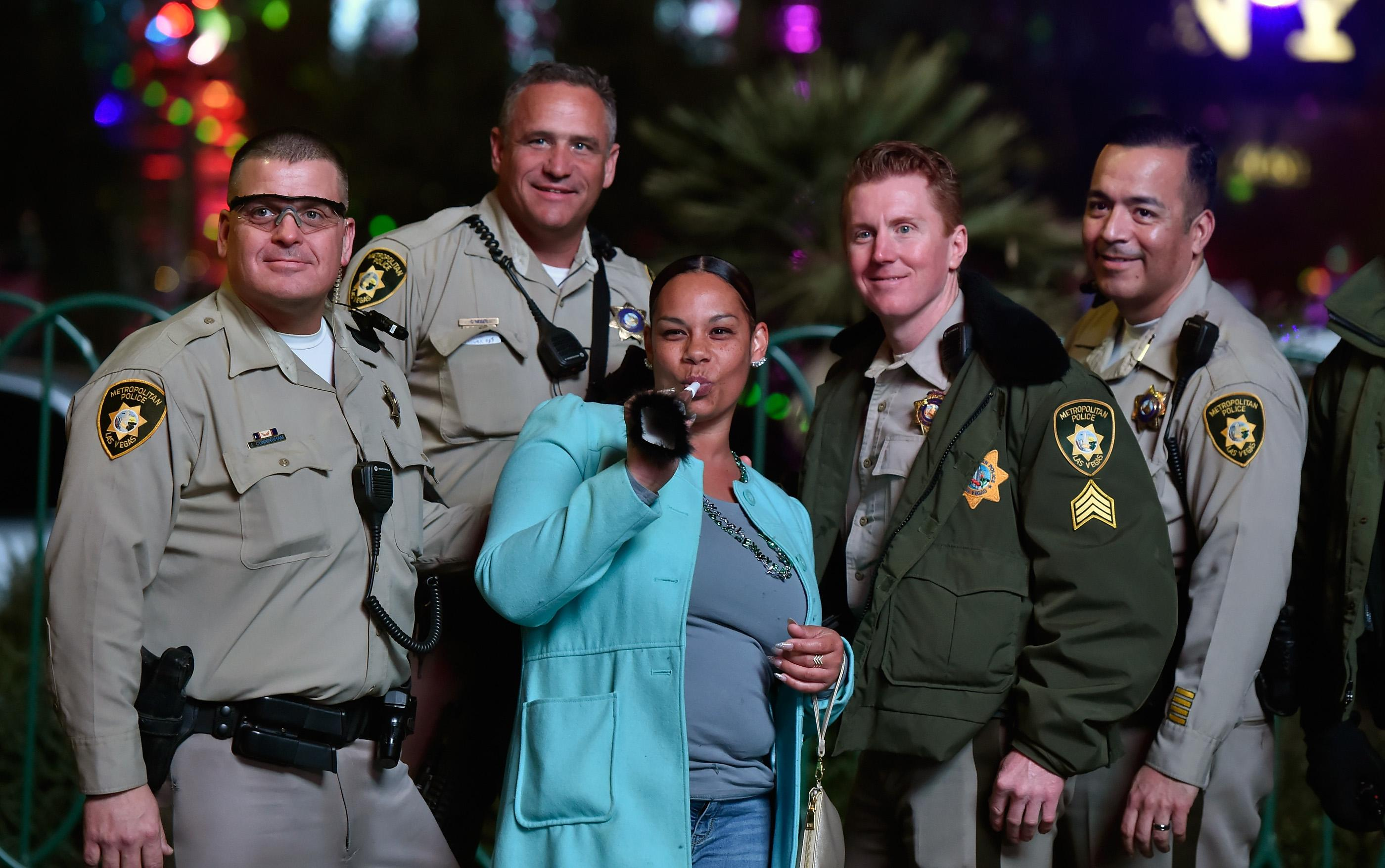 A reveler poses with members of the Las Vegas police as she celebrates New Year's Eve along the Las Vegas Strip Sunday, Dec. 31, 2017, in Las Vegas. CREDIT: David Becker/Las Vegas News Bureau
