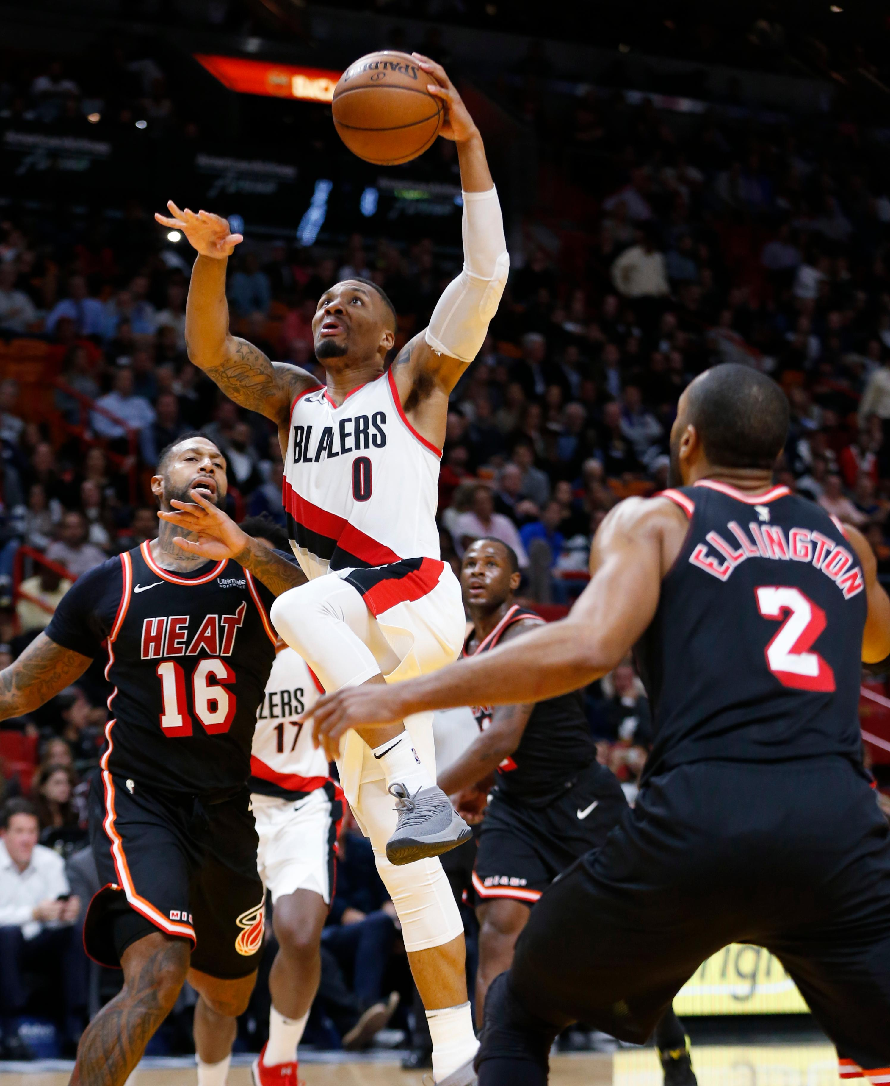 Portland Trail Blazers guard Damian Lillard (0) goes up for a shot against Miami Heat forward James Johnson (16) and guard Wayne Ellington (2) during the second half of an NBA basketball game, Wednesday, Dec. 13, 2017, in Miami. Lillard scored seven of his 18 points in the final 3:16 as the Trail Blazers defeated the Heat 102-95. (AP Photo/Wilfredo Lee)