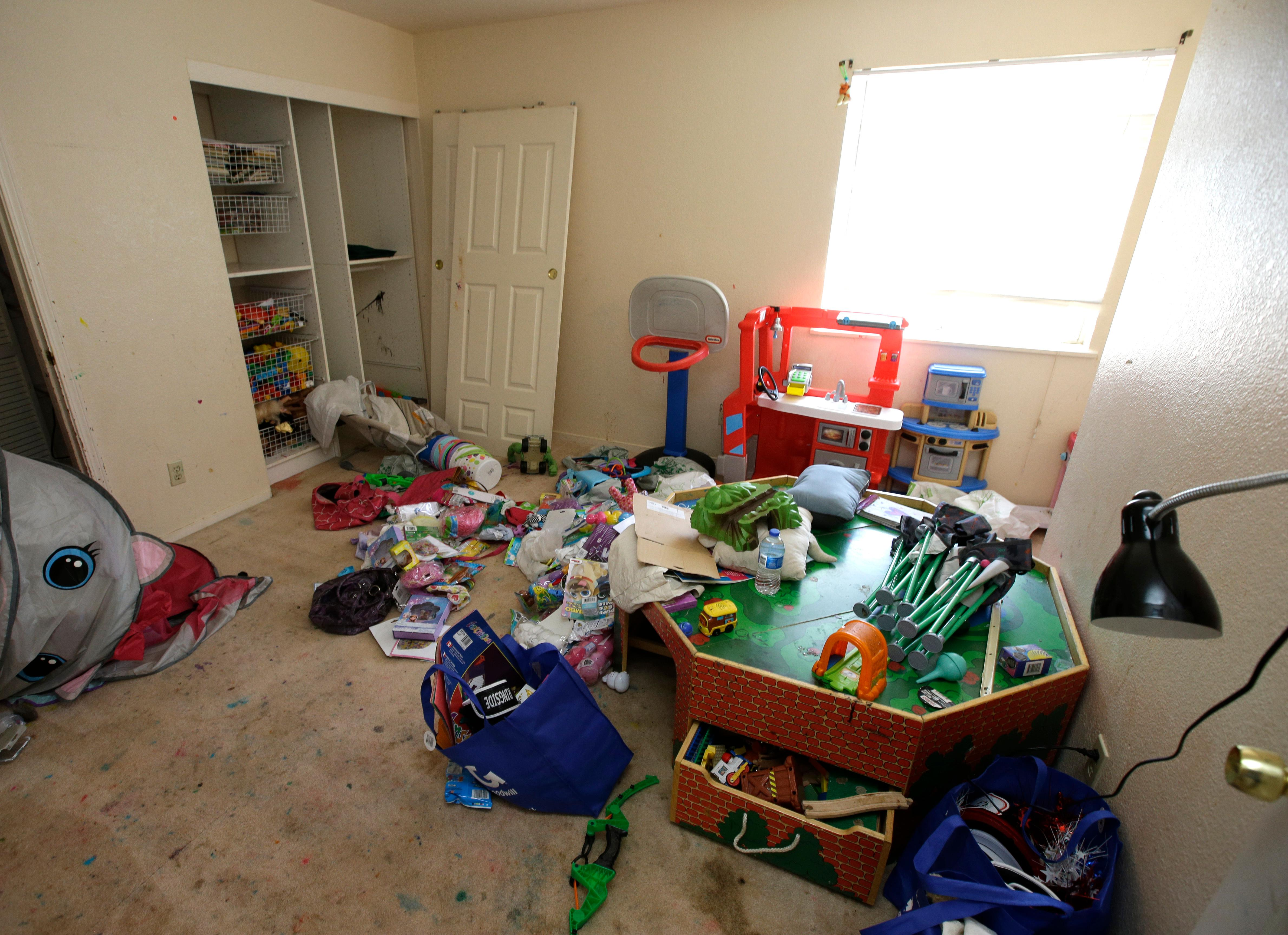 Toys and other items are strewn around one of the rooms of a home, Monday, May 14, 2018, where authorities removed 10 children and arrested their parents in Fairfield, Calif. Authorities removed the children living at the home on March 31 and placed them in protective custody after one of them ran away. Ina Rogers faces charges of child neglect and her husband, Jonathan Allen, has been charged with torture and child abuse. Ina Rogers denied the children were mistreated. (AP Photo/Rich Pedroncelli)