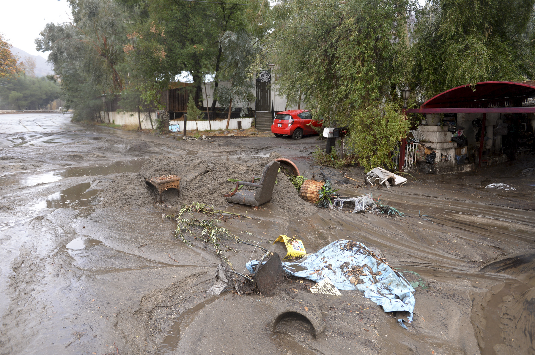 Mud washes away personal belongings along La Tuna Canyon road in the Sun Valley neighborhood of Los Angeles on Tuesday, Jan. 9, 2018. Homes were swept from their foundations  as heavy rain sent mud and boulders sliding down hills stripped of vegetation by Southern California's recent wildfires.   (David Crane/Los Angeles Daily News via AP)