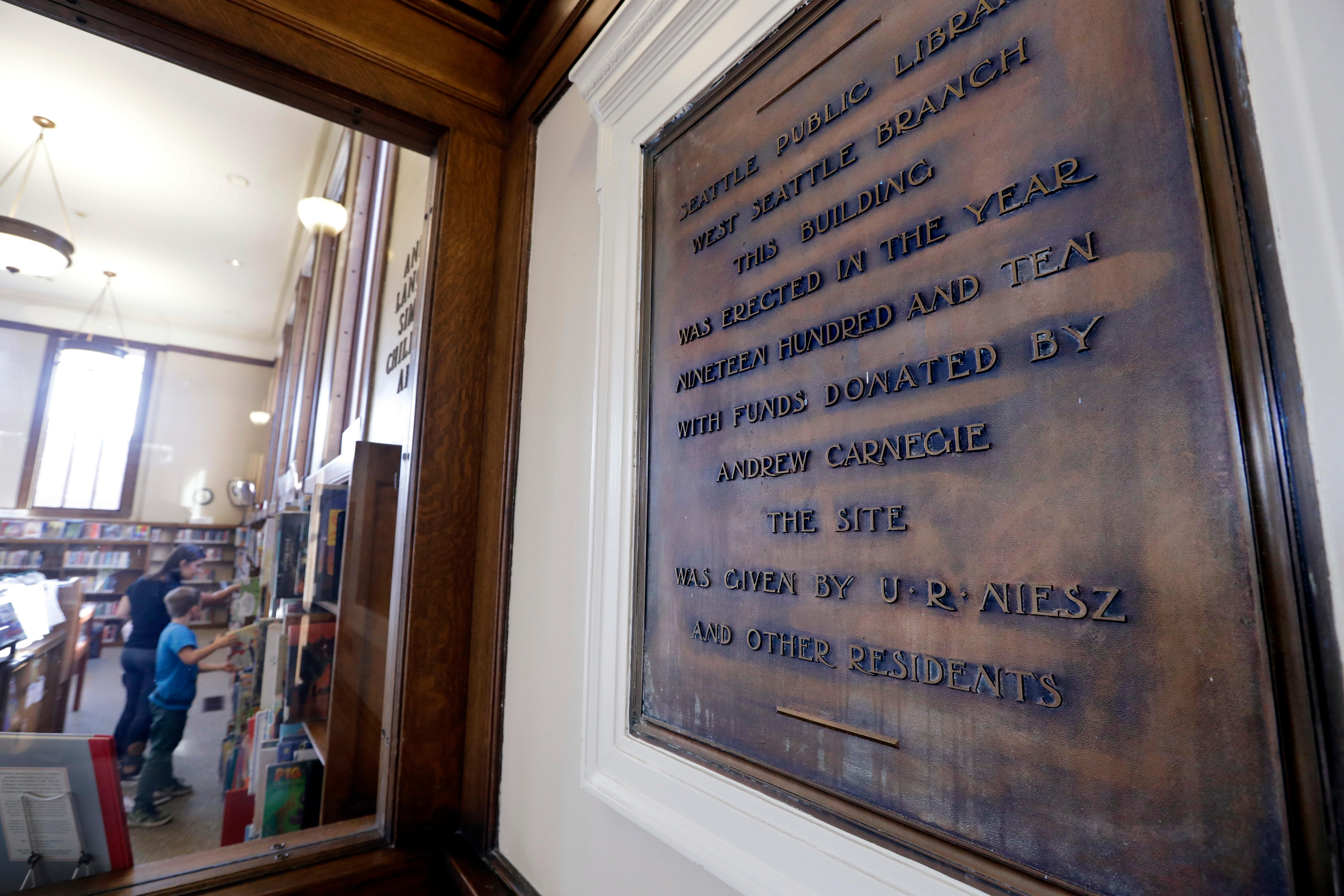 In this photo taken Wednesday, Oct. 10, 2018, library patrons look over books in view of a plaque honoring the Andrew Carnegie-built Seattle Public Library, one of six in the city still in use that were built with funds from the philanthropist, in Seattle. (AP Photo/Elaine Thompson)