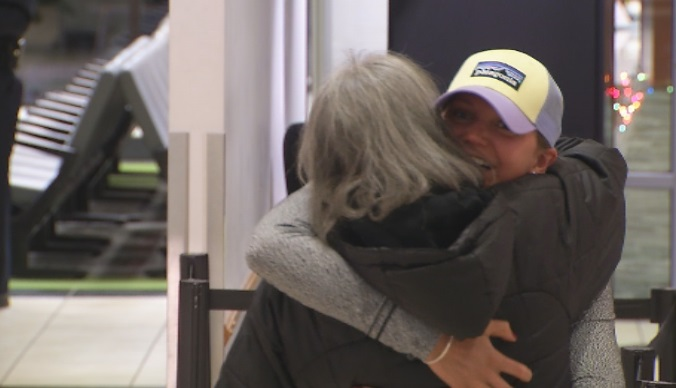 Lt. Nicki Warner hugs her mother after stepping off of a plane at Yeager Airport late Tuesday night. (WCHS/WVAH)