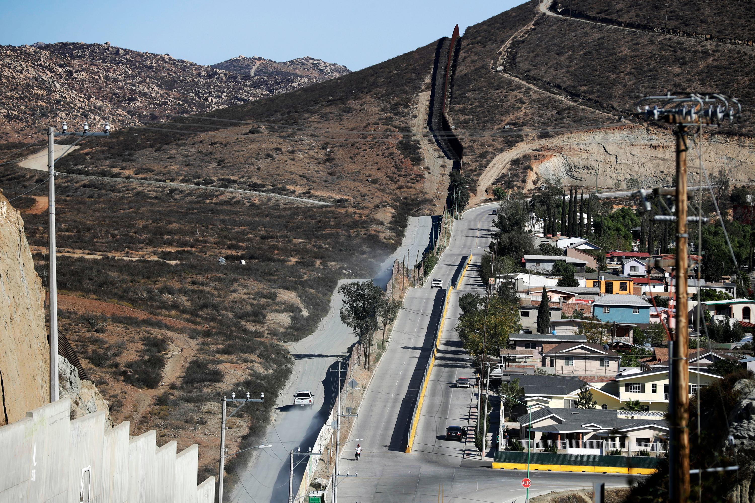 FILE - In this Nov. 9, 2016 file photo, a Border Patrol vehicle drives by the border fence in Tecate, Calif., left, along the metal barrier that lines the border, seen from Tecate, Mexico. (AP Photo/Gregory Bull, File)<p></p>