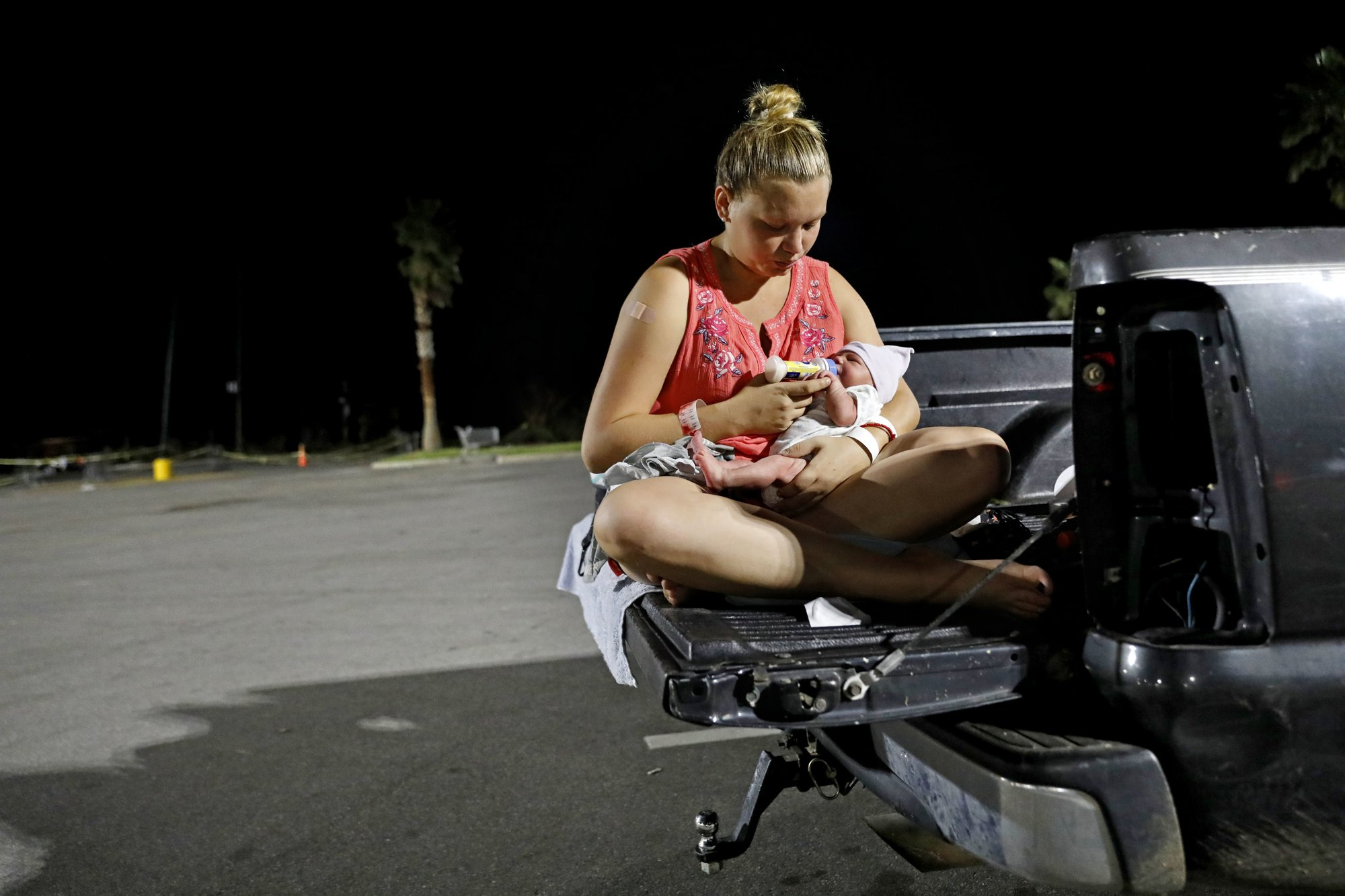 Lorrainda Smith, feeds her two-day-old son Luke out of the back of her pickup truck while preparing to spend the first night out of the hospital with her newborn and husband Wilmer Capps in a parking lot in Panama City, Fla., Monday, Oct. 15, 2018, as their home was badly damaged from Hurricane Michael. (AP Photo/David Goldman)
