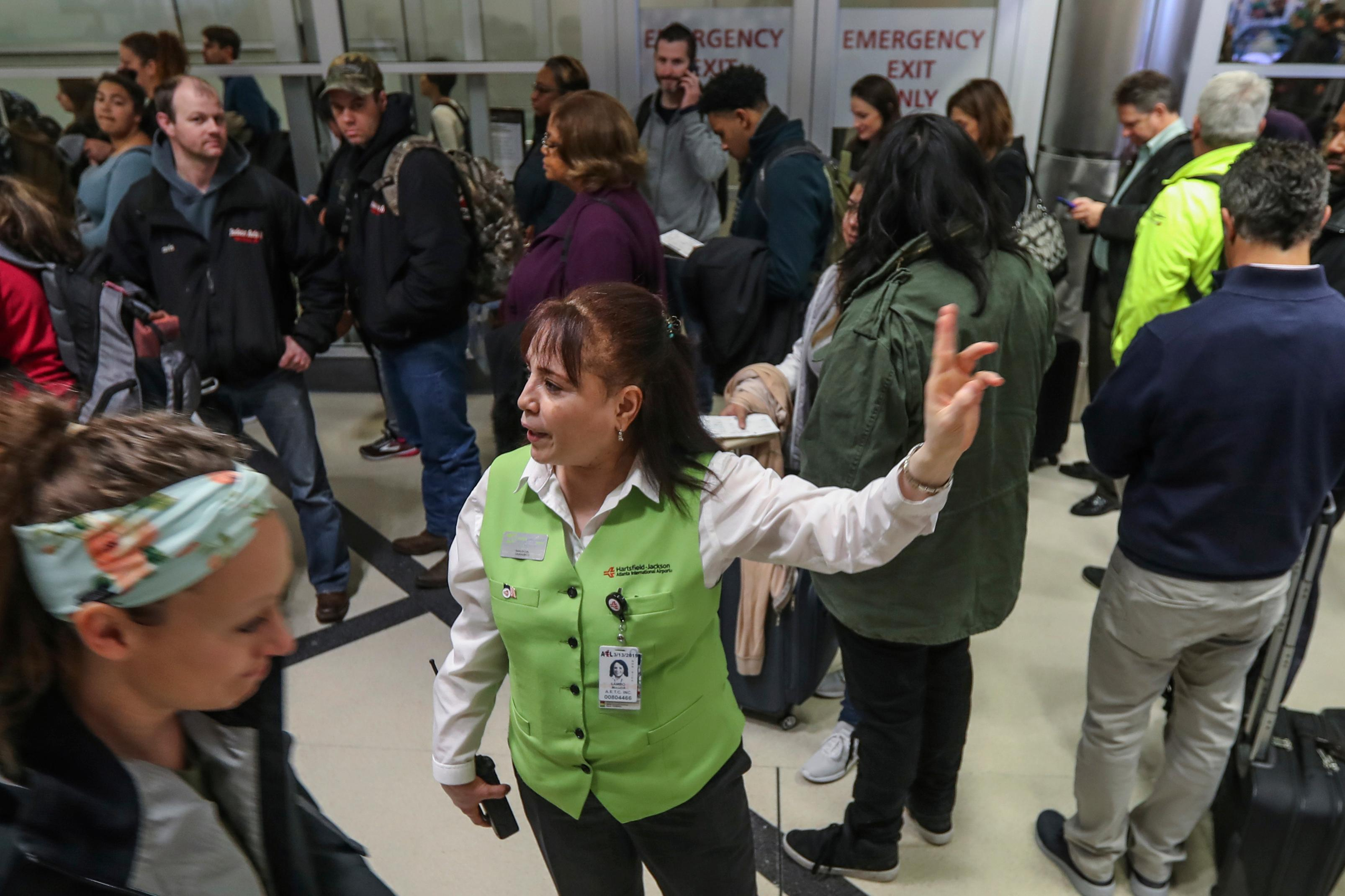 Customer Service representative Magda Lambo, center, directs travelers as security lines at Hartsfield-Jackson International Airport in Atlanta stretch more than an hour long amid the partial federal shutdown, causing some travelers to miss flights, Monday morning, Jan. 14, 2019. The long lines signaled{ }staffing shortages{ }at security checkpoints, as TSA officers have been working without pay since the federal shutdown began Dec. 22. (John Spink/Atlanta Journal-Constitution via AP)