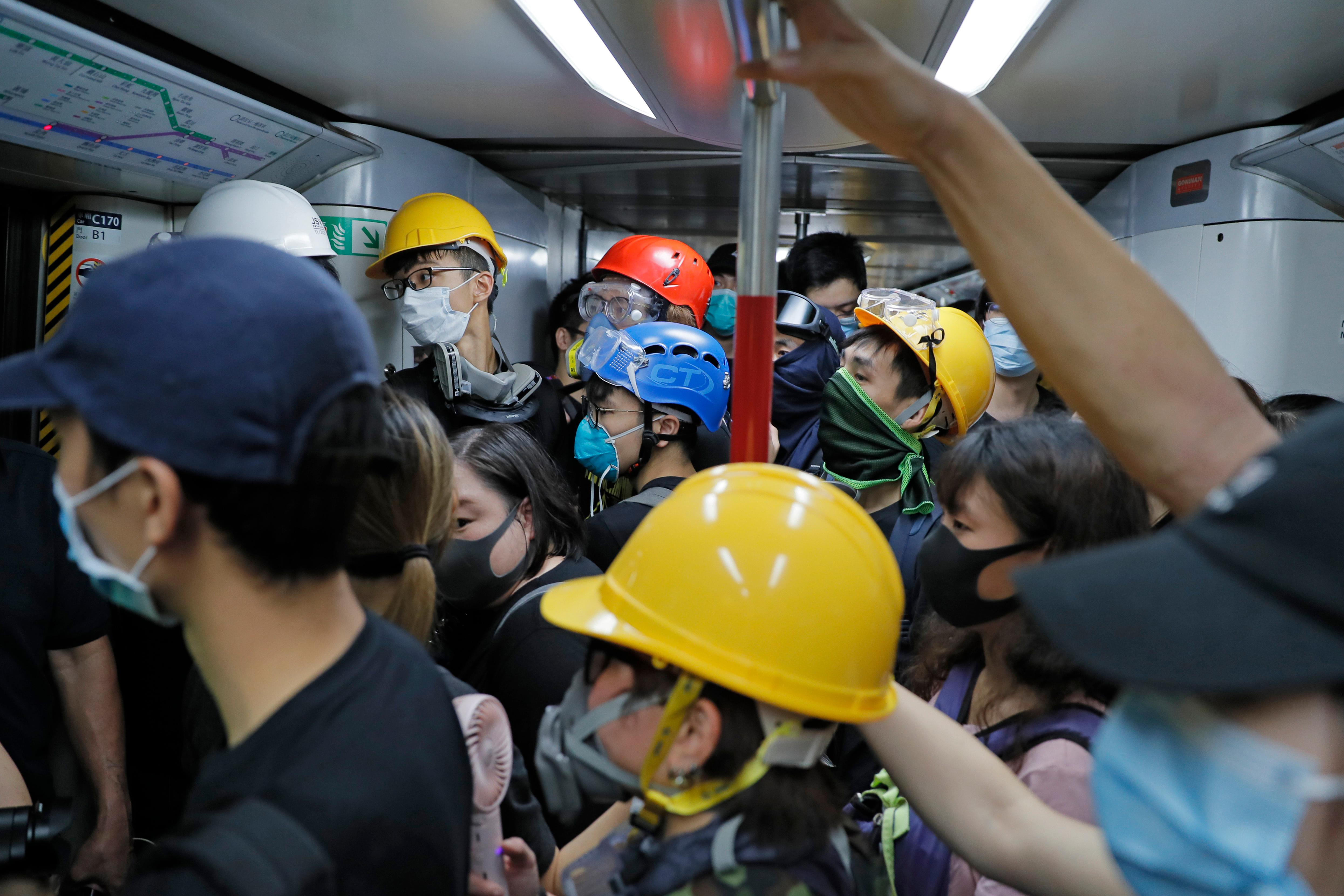 Protesters with protective gear take a train to the anti-extradition bill protest destination, in Hong Kong on Sunday, Aug. 4, 2019. Demonstrators in Hong Kong moved en masse to a luxury shopping district Sunday evening after riot police used tear gas to clear out an area they were previously occupying, as the 2-month-old protest movement showed no signs of easing. (AP Photo/Kin Cheung)